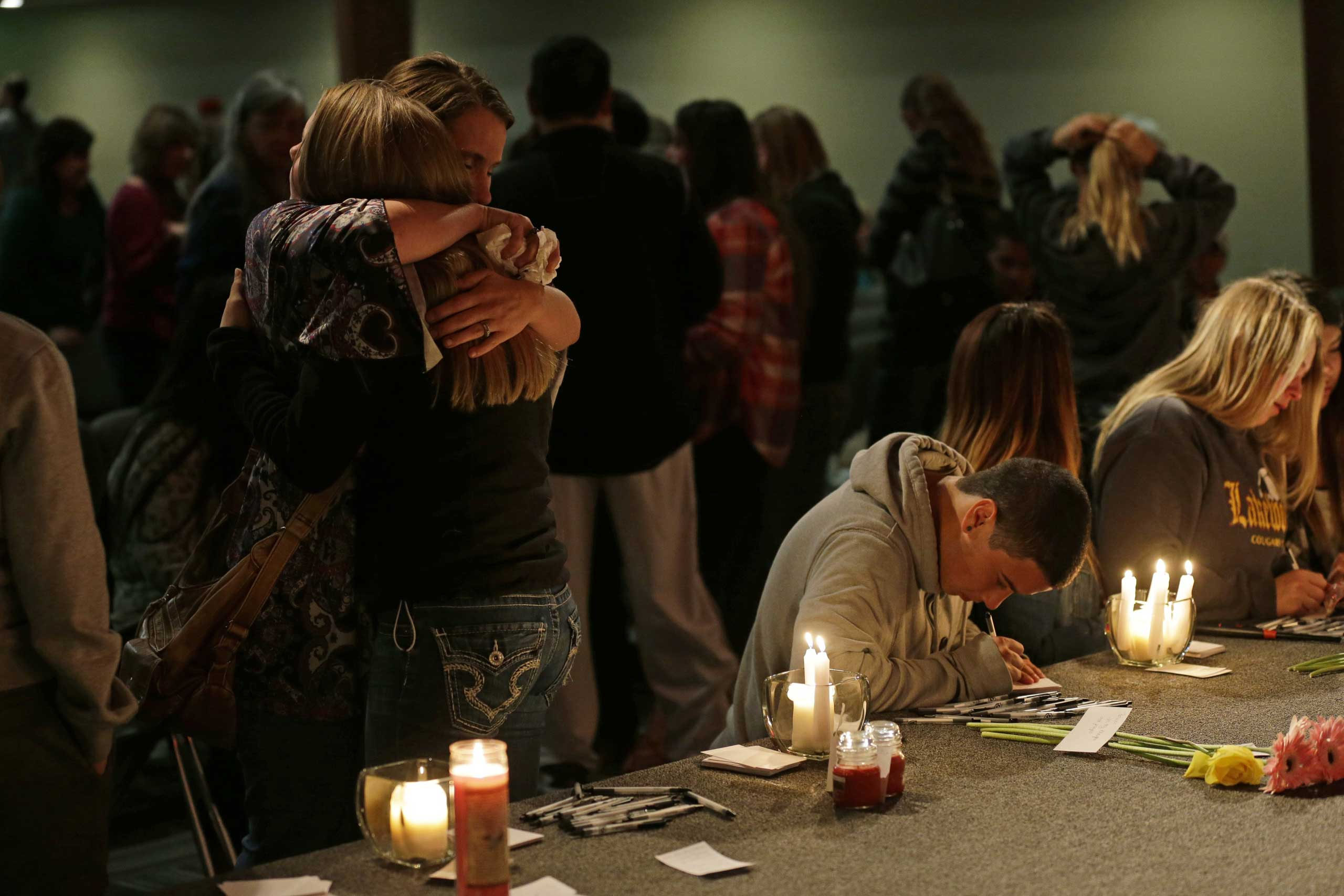 Oct. 24, 2014. Two people hug as others write messages on paper following a memorial vigil at the Grove Church in Marysville, Wash., for people affected by a shooting at Marysville Pilchuck High School earlier in the day.