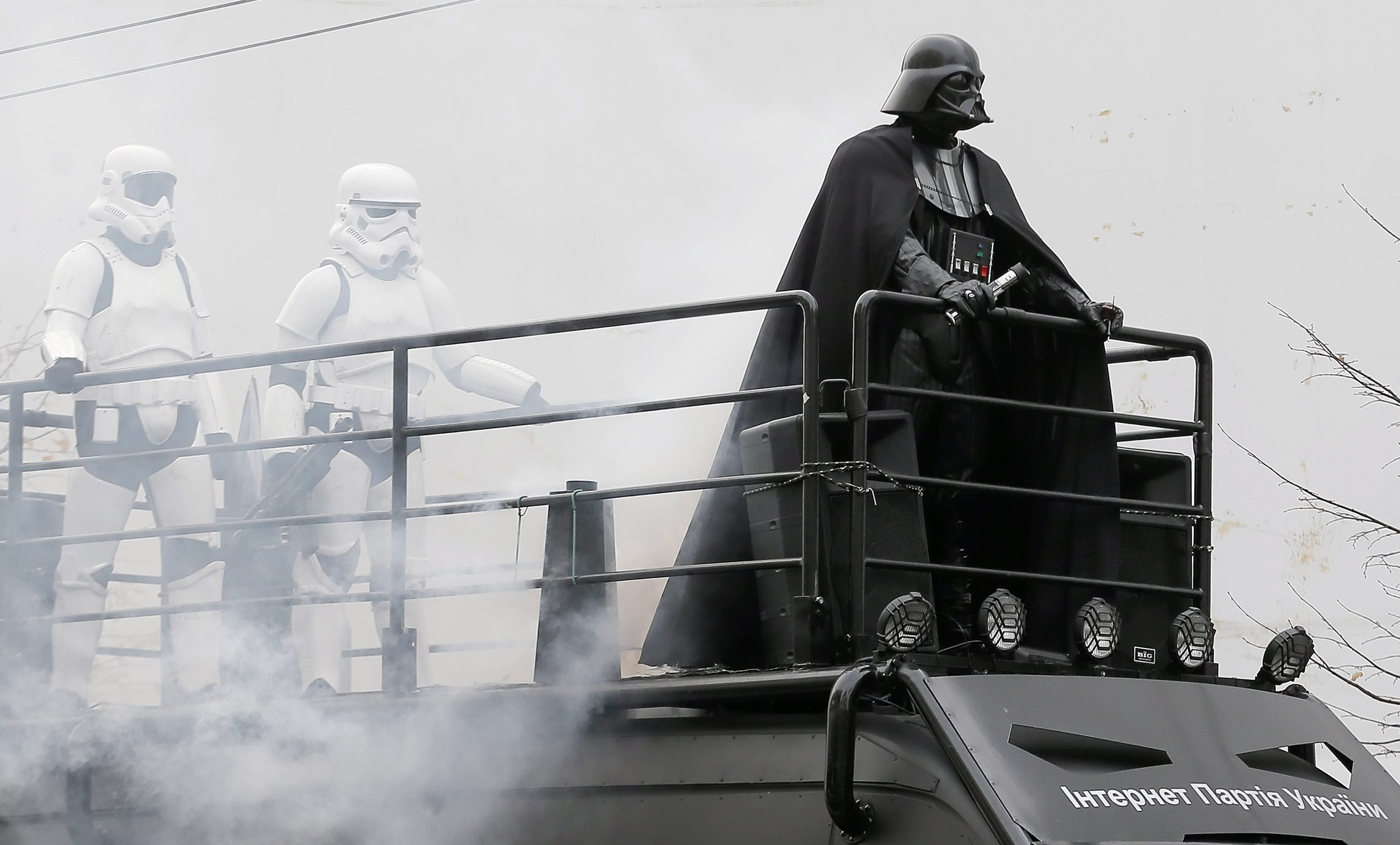 An impersonator of Star Wars character 'Darth Vader' stands with some storm troopers on the roof of a campaigning van during an election campaign event for the Ukrainian Internet Party, in downtown Kiev, Ukraine on Oct. 21, 2014.