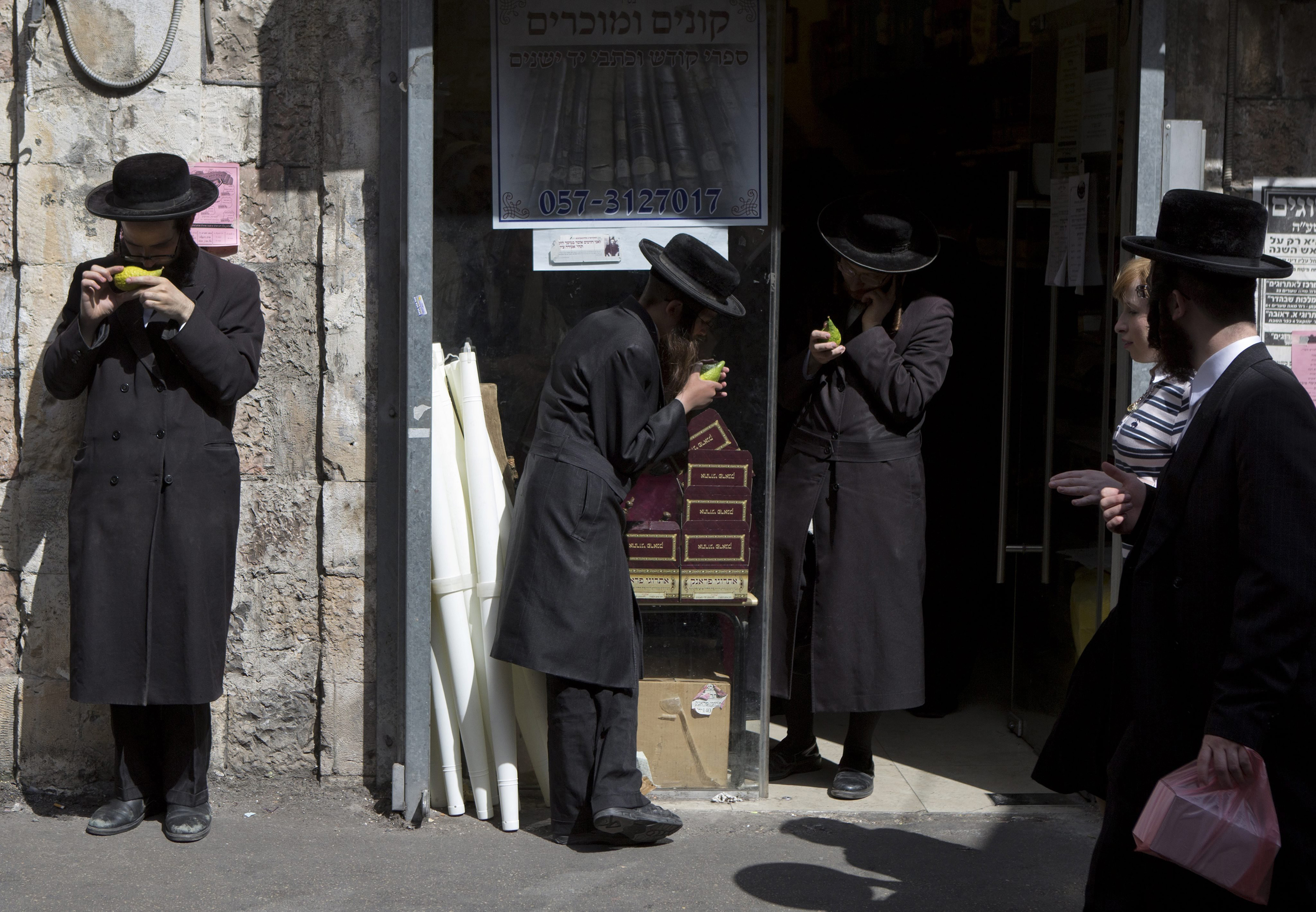Ultra-Orthodox Jews inspect etrogs, or citrons, outside a shop in the Mea Shearim neighborhood of Jerusalem, Oct. 7, 2014.