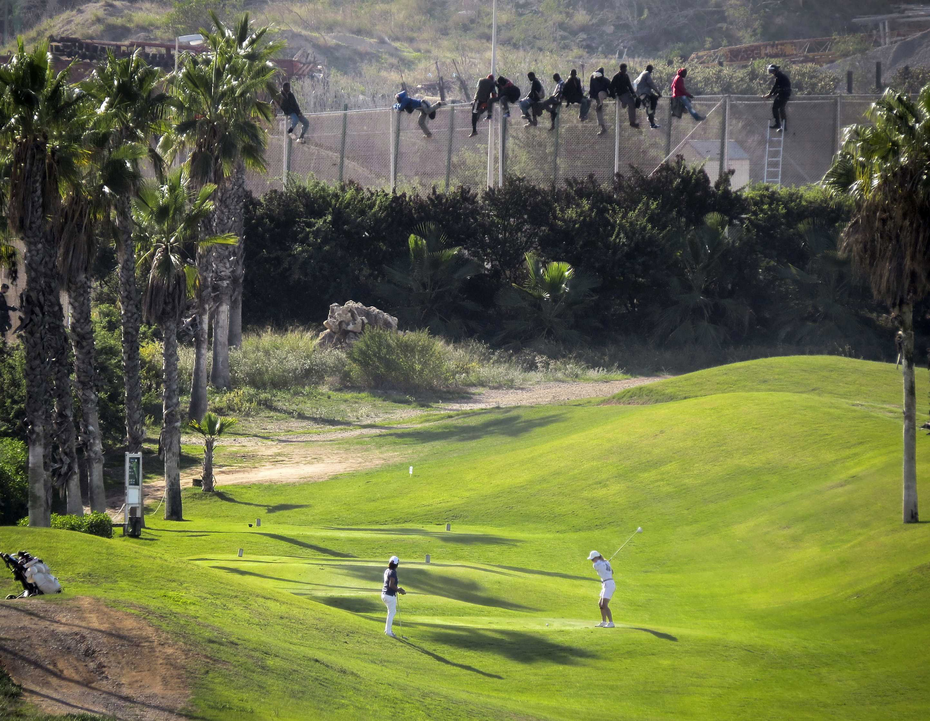 A golfer hits a tee shot as African migrants sit atop a border fence during an attempt to cross into Spanish territories between Morocco and Spain's north African enclave of Melilla on Oct. 22, 2014.