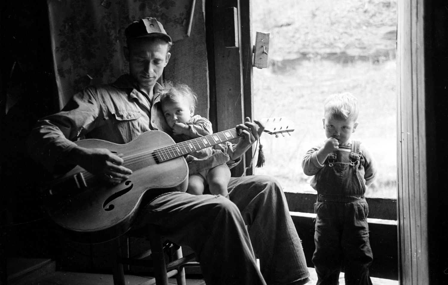Caption from LIFE. Family life in Leslie County's mountains has the warmth of a father singing to his children.