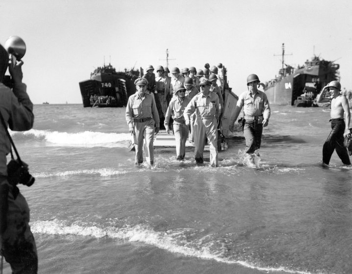 Gen. Douglas MacArthur with Gen. Richard Sutherland (left) and Col. Lloyd Lehrbas (second from left) walks through the surf to the beach at Lingayen, Luzon, the Philippines, Jan. 9, 1945.
