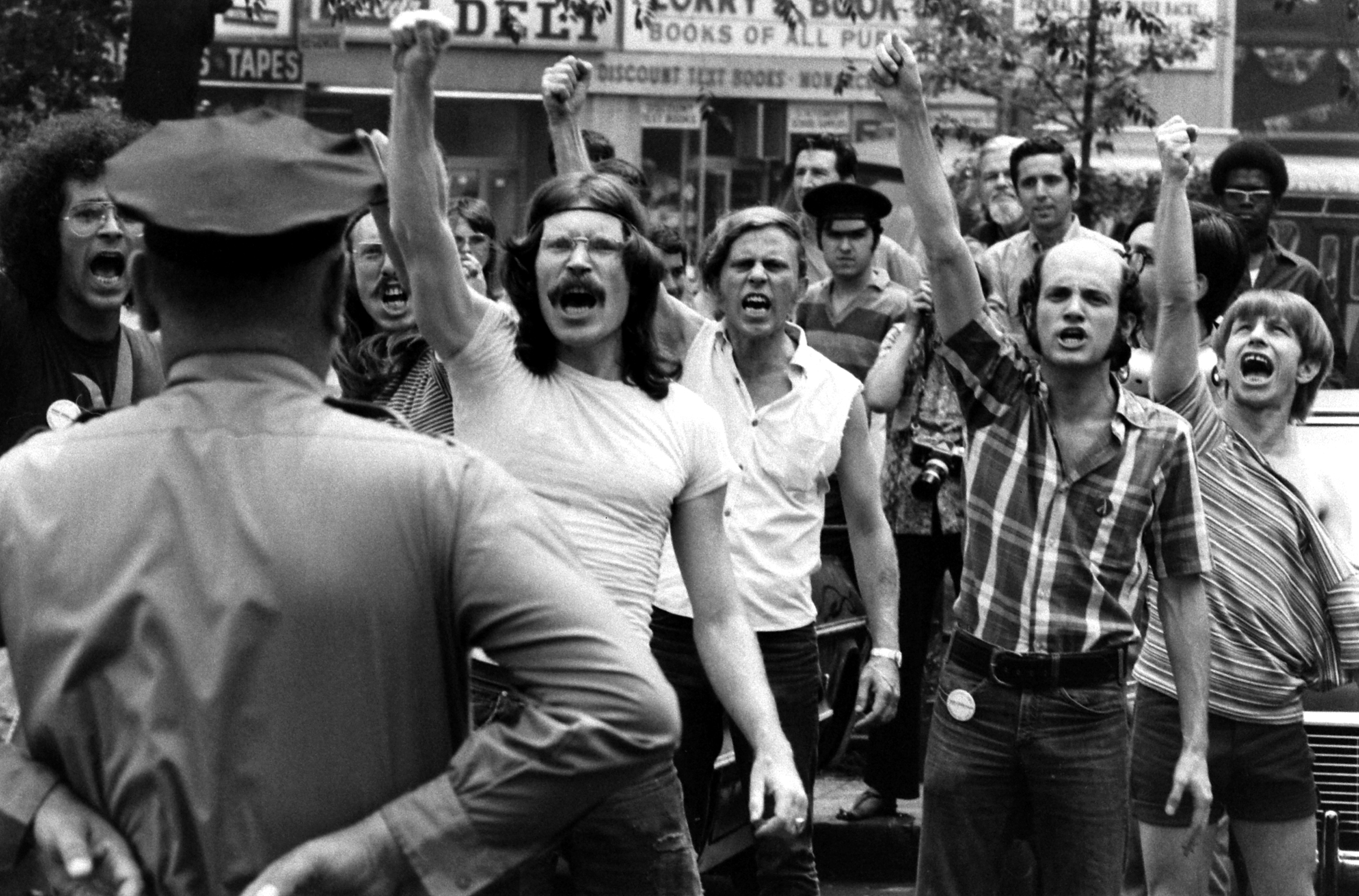 "<b>Caption from LIFE</b> When a bill guaranteeing equal job opportunities for homosexuals stalled in New York City Council last spring, militants demonstrated at City Hall. With fists raised, they shout a football style ""Gay Power"" cheer at police blocking the building."
