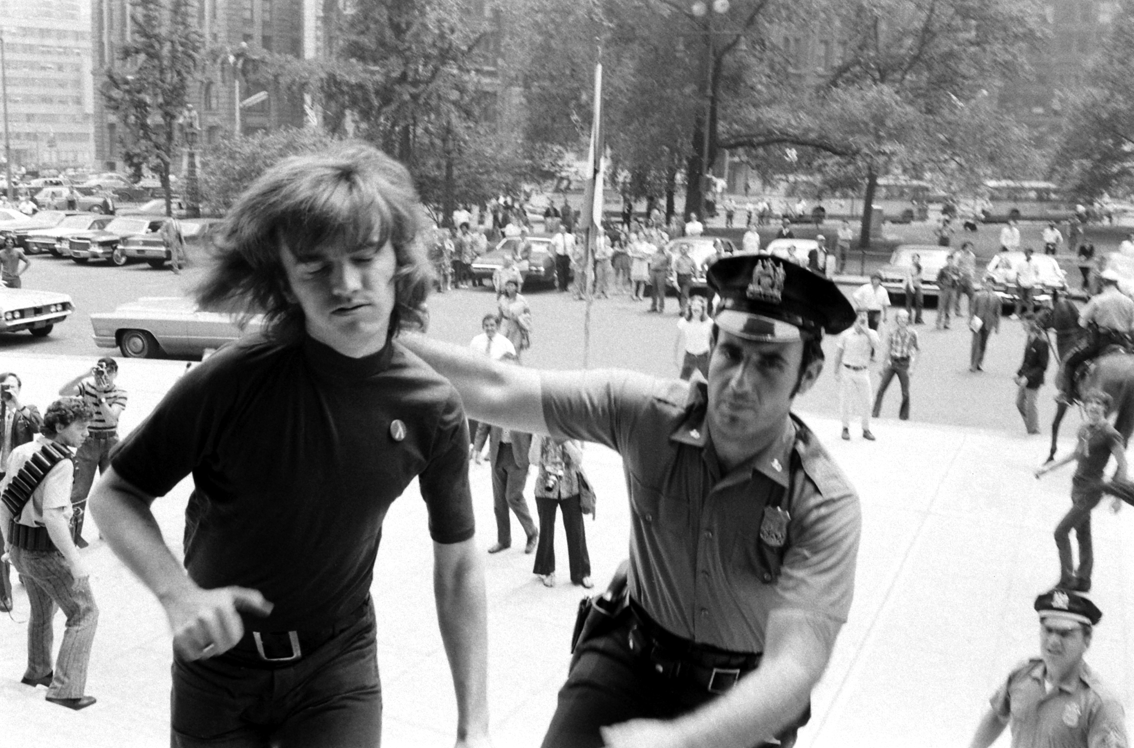 <b>Caption from LIFE</b> Collared by a patrolman after he deliberately crossed police barricades at New York's City Hall, Gay Activists Alliance President Jim Owles submits to arrest. Members of his organization were protesting City Council reluctance to debate a fair employment bill for homosexuals.