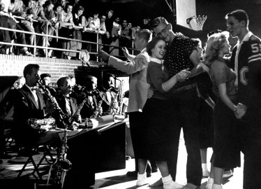 """In aura of fun and well-being, students dance in gym of Carlsbad's high school at weekly """"Sock Hop"""" to music of a 12-piece student band."""
