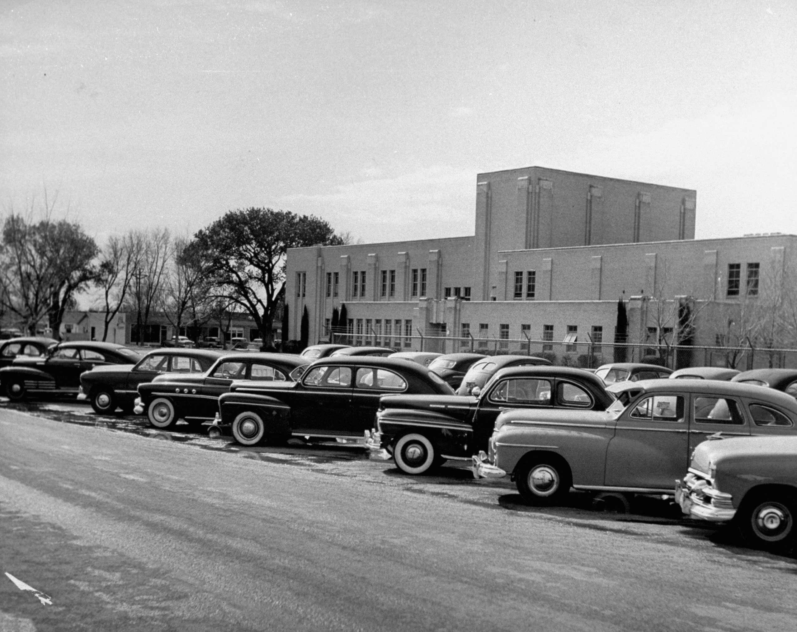 <b>Caption from LIFE.</b> Cars of Carlsbad High students fill own parking lot.