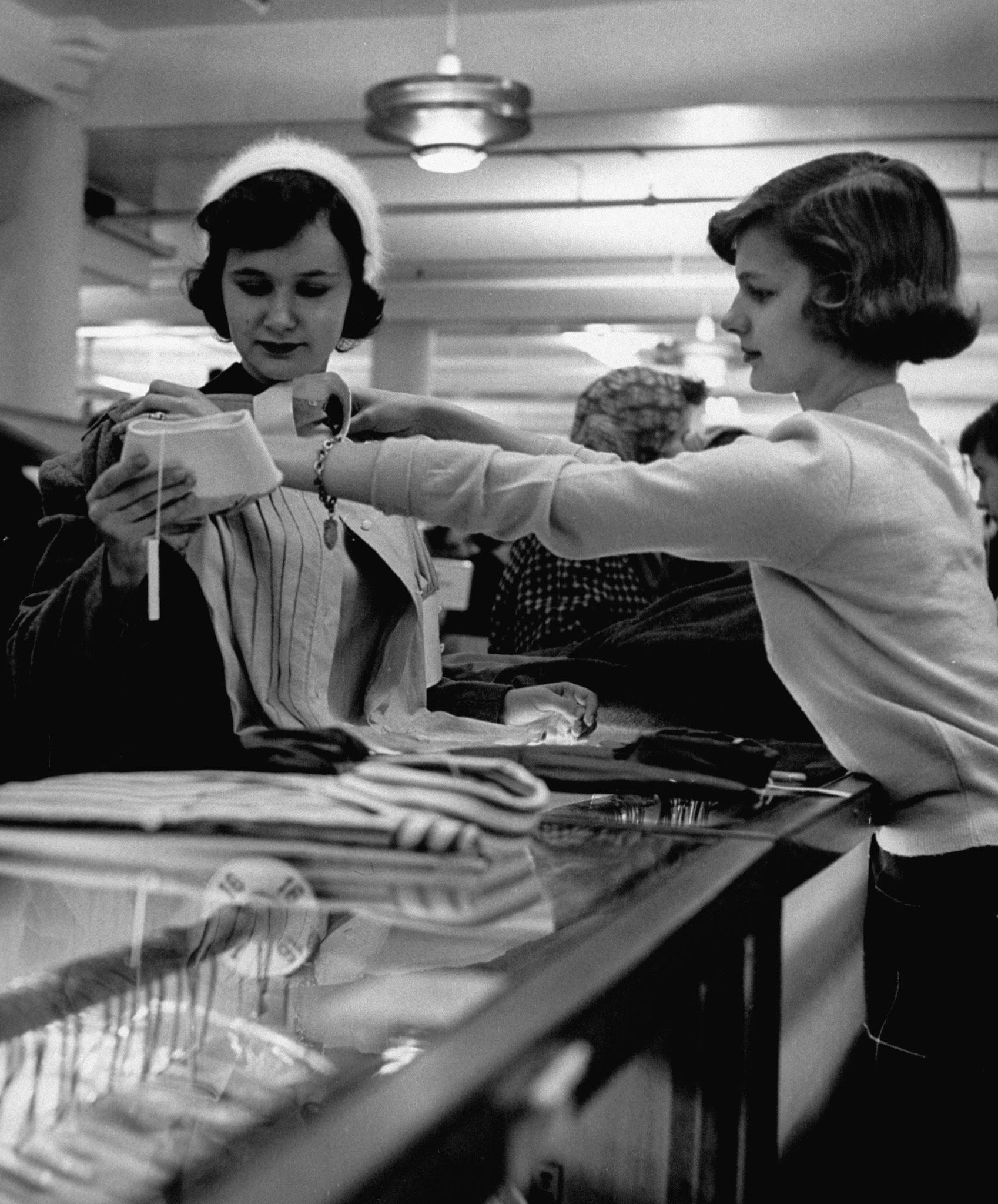 <b>Caption from LIFE.</b> Attractive young sales girl holding blouse up to customer in store, as customer is looking at other things to buy.
