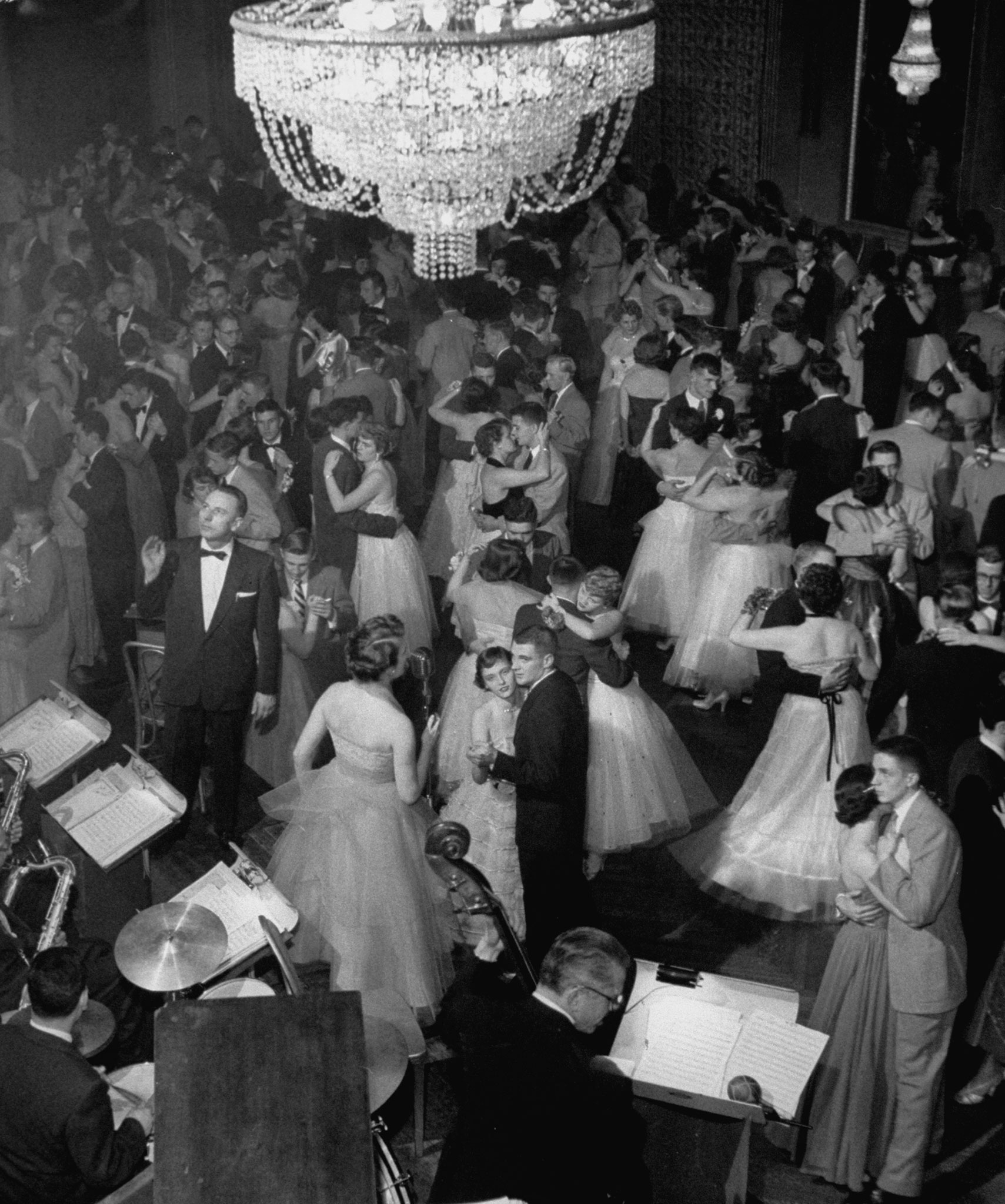 <b>Caption from LIFE.</b> Young couples at formal dance dreamily swaying on crowded floor of dim, chandelier-lit ballroom.
