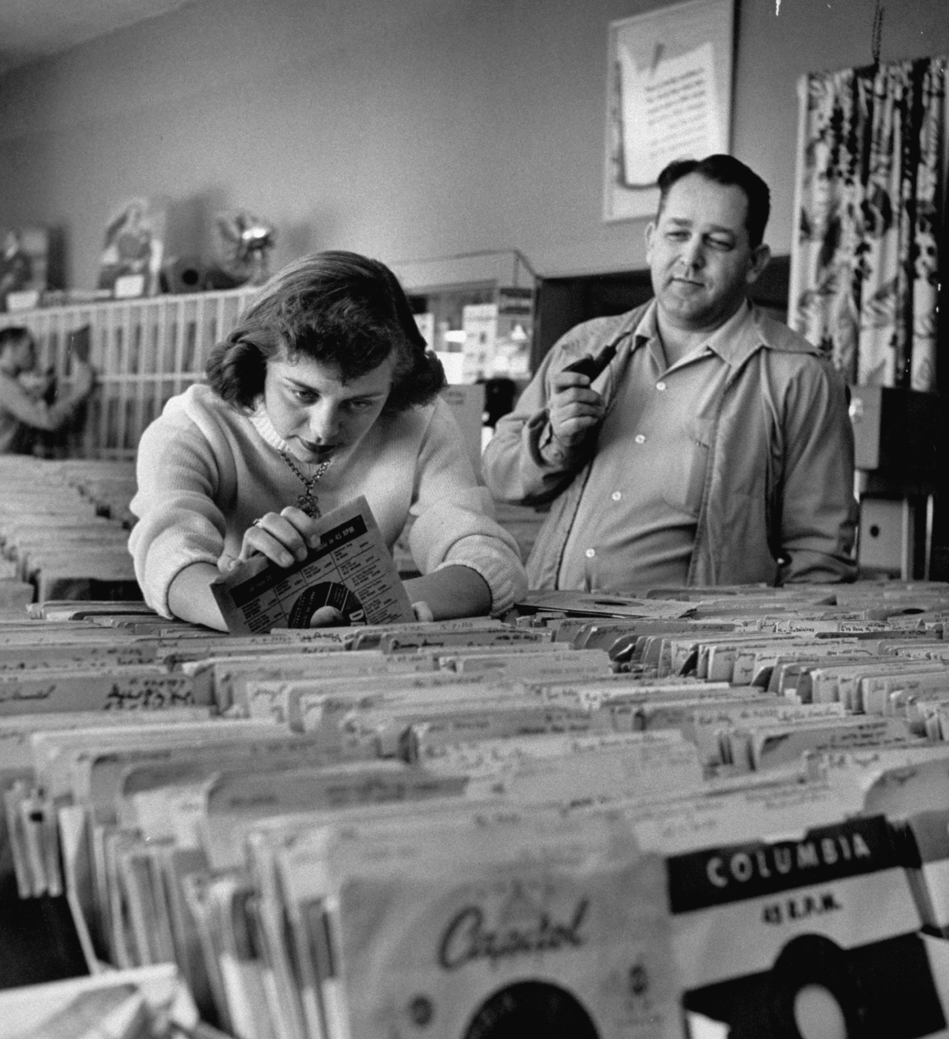<b>Caption from LIFE.</b> Pay in trade is taken by Margaret High, 17, who works in music store, spends salary on records.