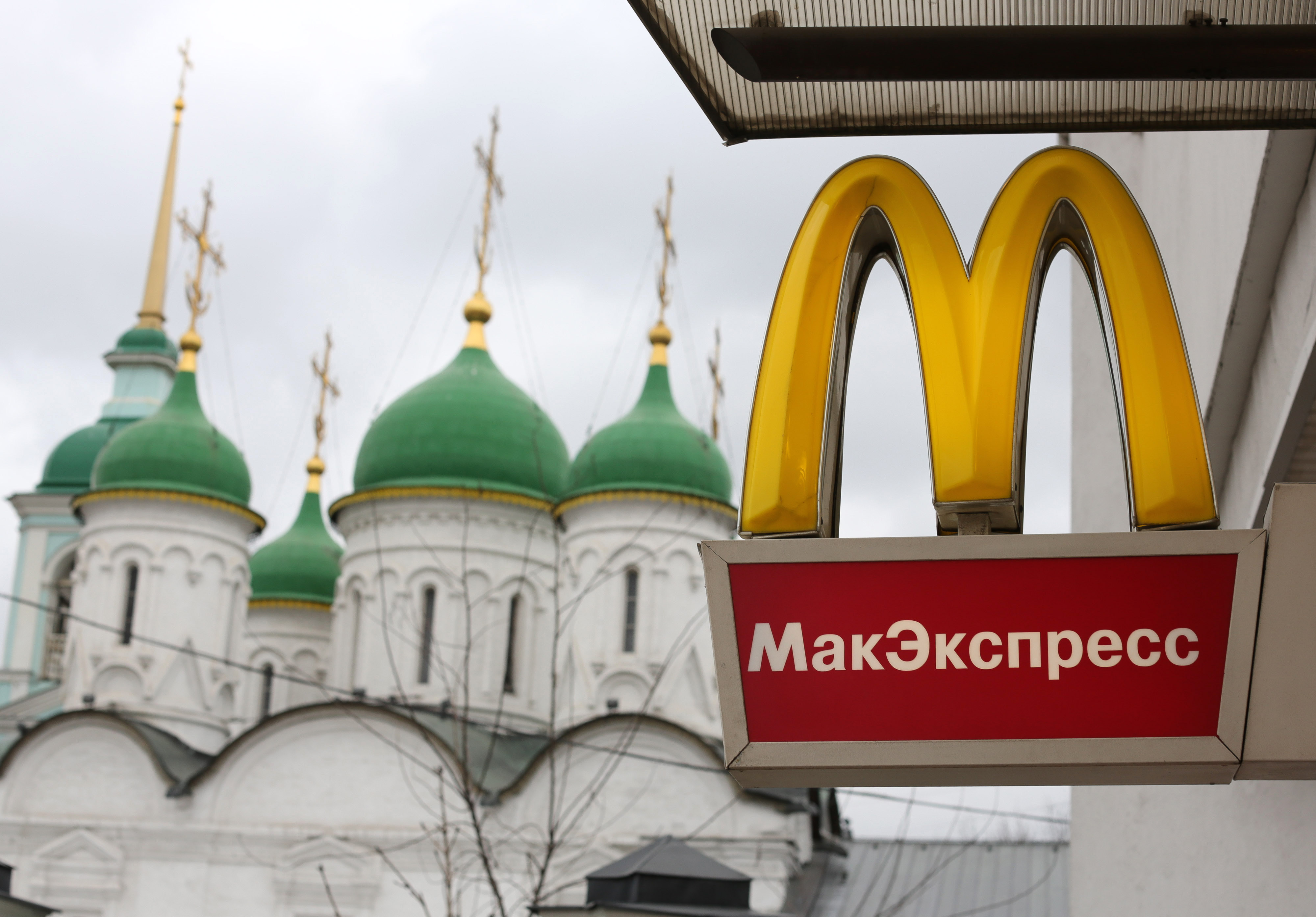 A logo hangs on display outside a McDonald's food restaurant in Moscow, Russia, on Sunday, April 7, 2013.