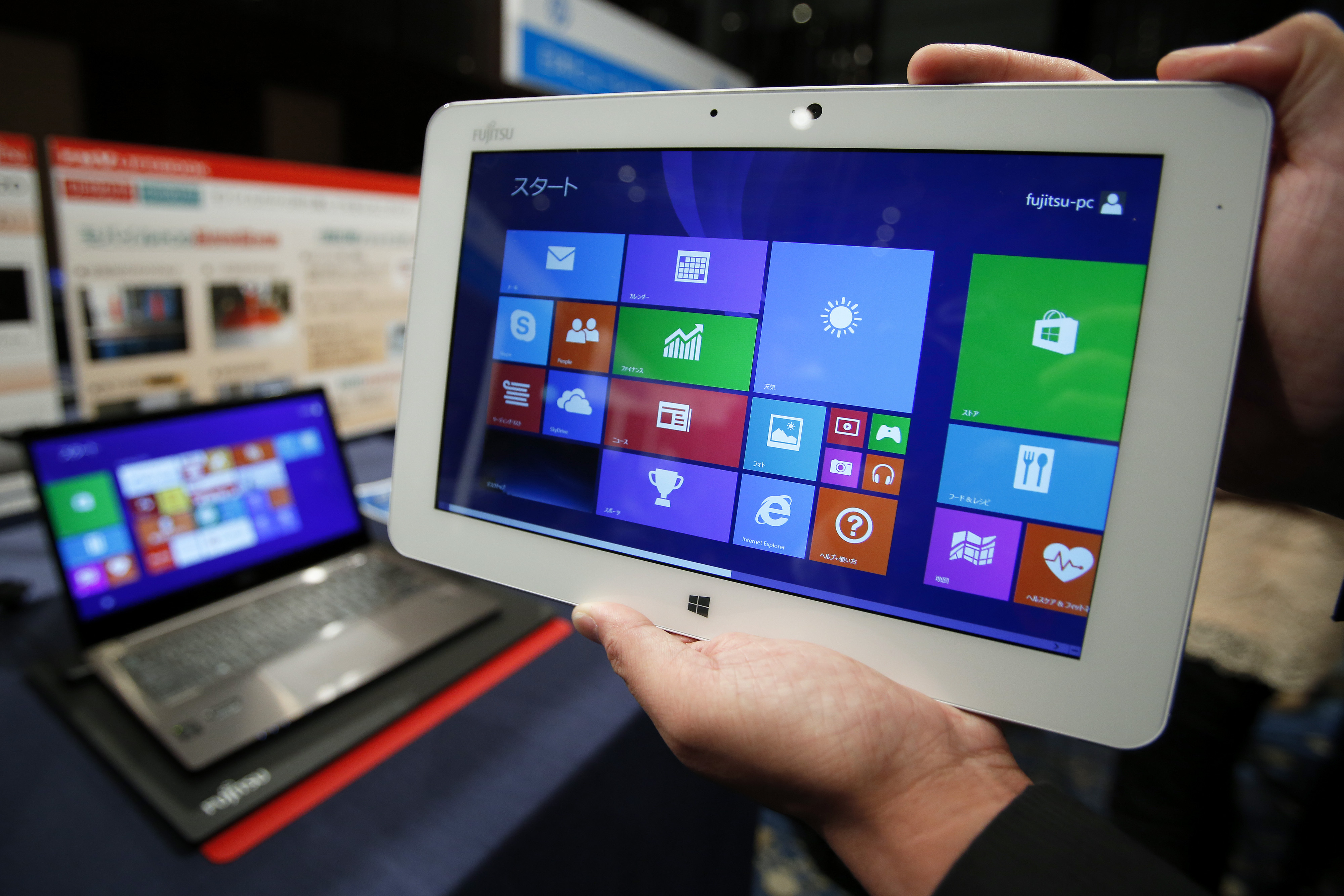 An attendant displays a Fujitsu Ltd. Arrows Tab tablet, running Microsoft Corp.'s Windows 8.1 operating system, during a launch event for the operating system in Tokyo, Japan, on Friday, Oct. 18, 2013.