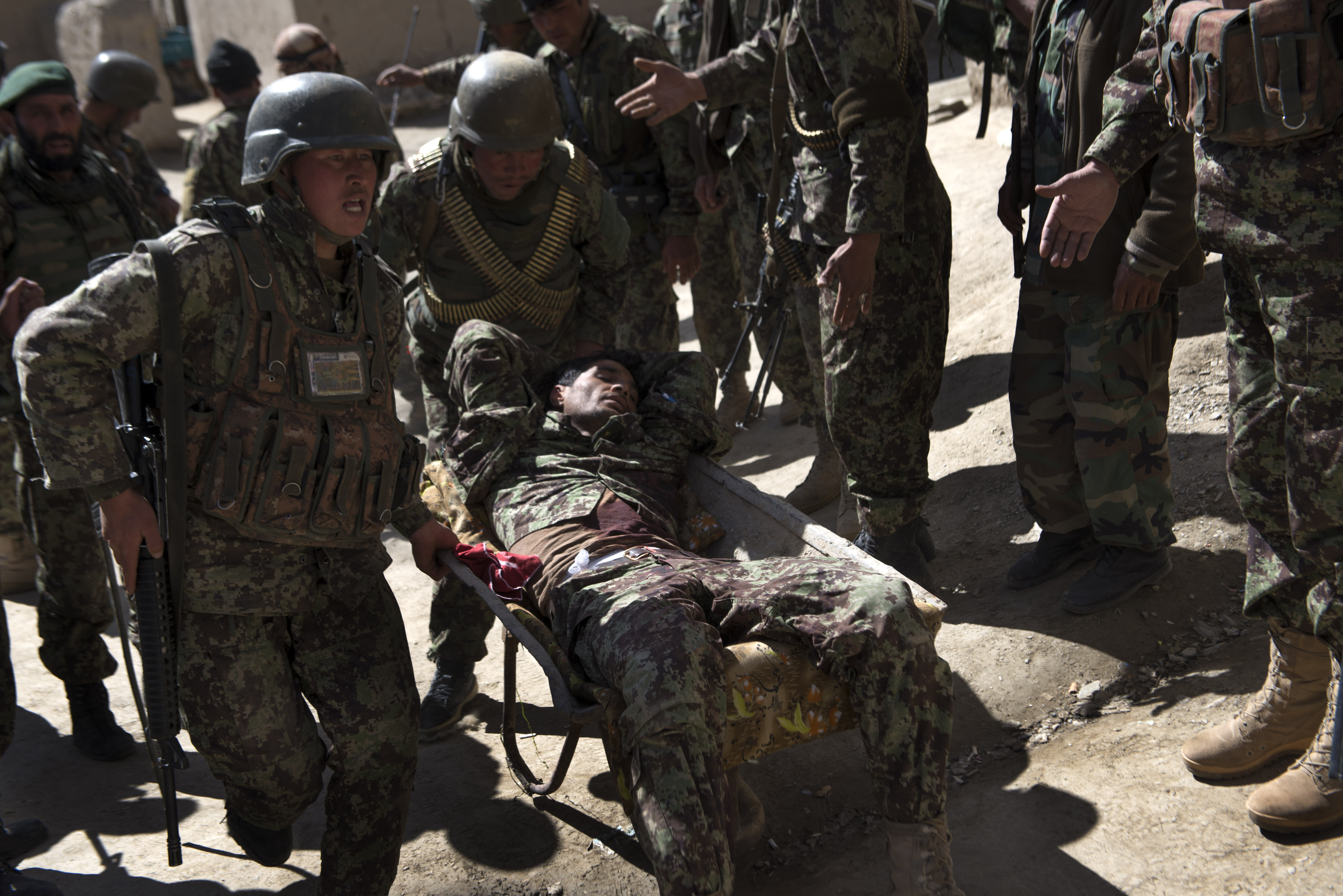 Afghan Army soldiers carry their comrade in a wheel-barrow after he was shot during a firefight on Tuesday April 2, 2013 in Wardak Province.
