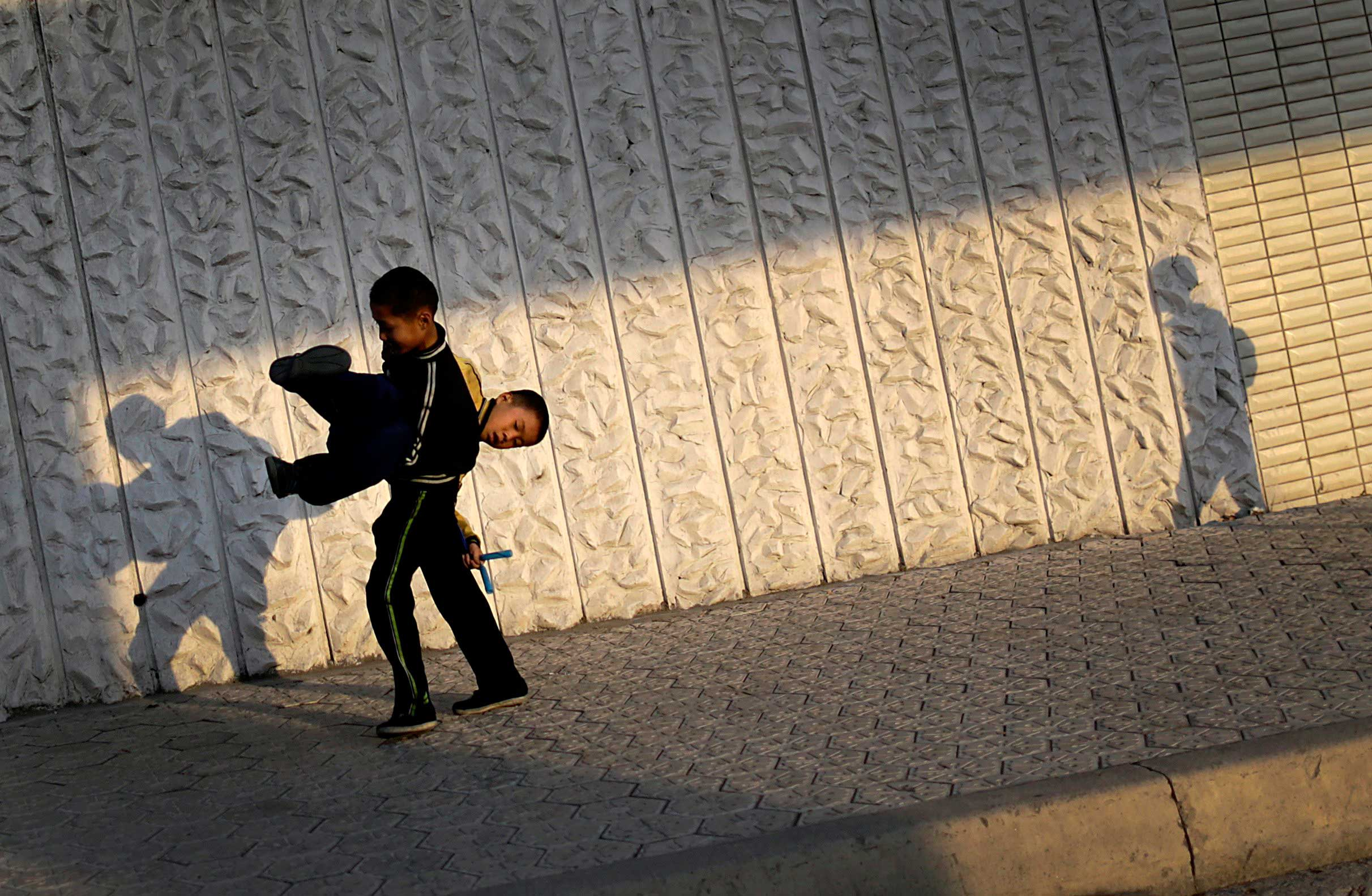 Oct. 22, 2014. The evening sun casts shadows of North Korean boys on an apartment building facade as they make their way down a street in Pyongyang, North Korea.