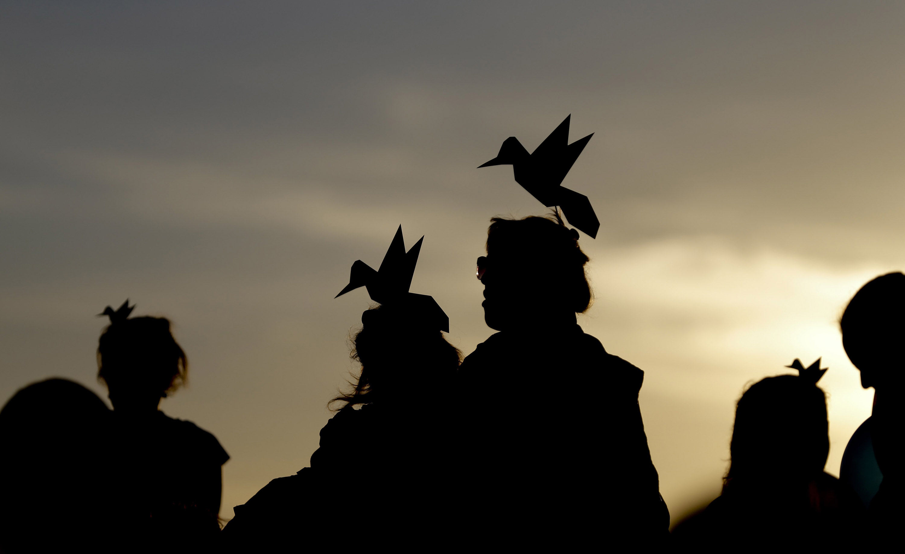 Supporters of presidential candidate for the ruling Broad Front party, Tabare Vazquez, wear paper birds on their heads, while attending his closing campaign rally in Montevideo, Uruguay on Oct. 23, 2014.