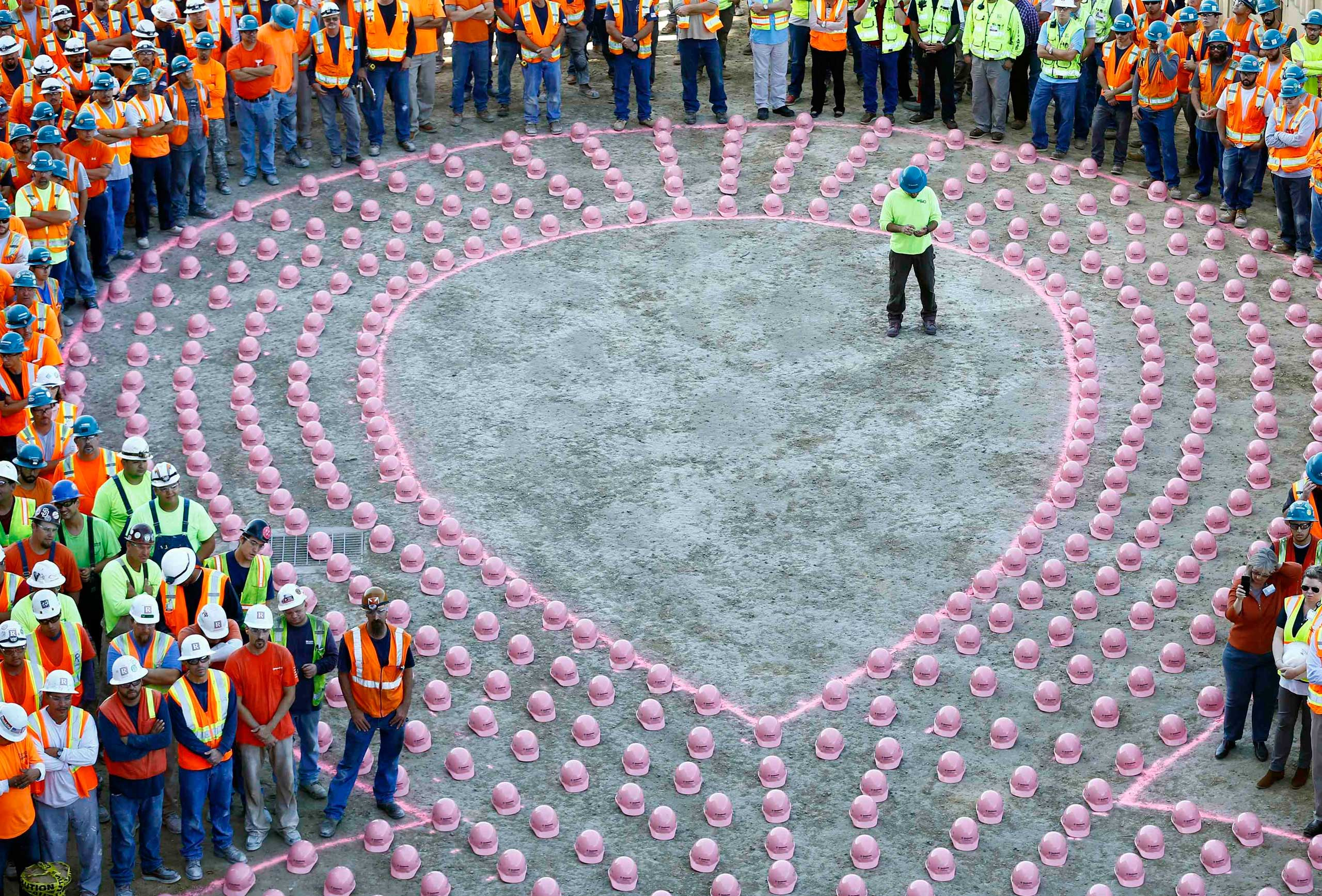 Sept. 30, 2014. Construction workers from EMCOR Dynalectric wait to put on pink hard hats and be part of a giant pink ribbon formation to promote the start of  Breast Cancer Awareness Month, at the UC San Diego Jacobs Medical Center construction site in  La Jolla, California.