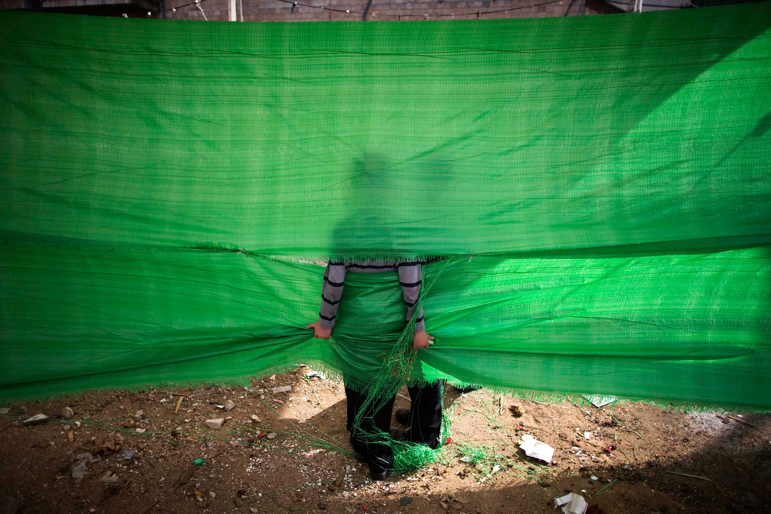 Oct. 1, 2014. An ultra-Orthodox Jewish boy holds on to a tarp in Jerusalem's Mea Shearim neighborhood ahead of Yom Kippur, the Jewish Day of Atonement, which starts at sundown on Friday.