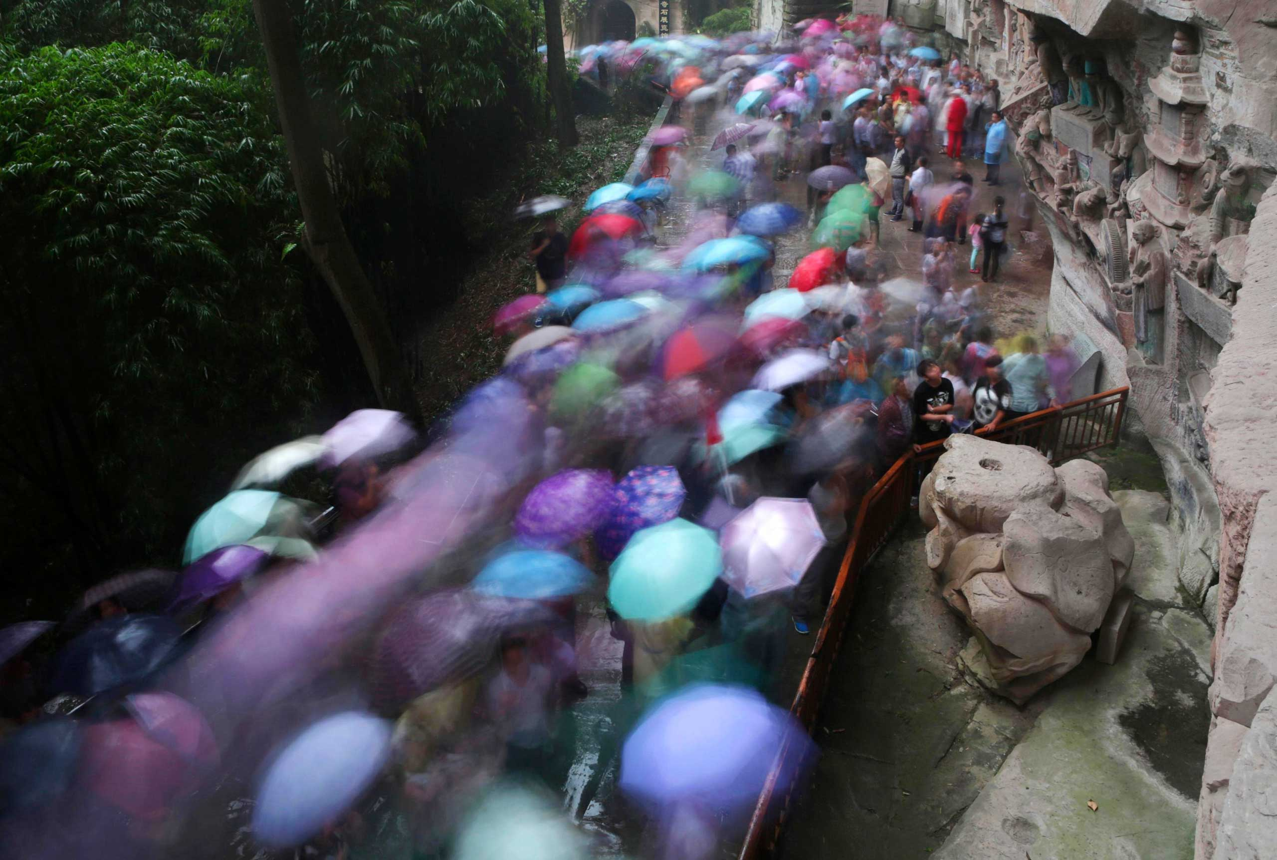 Oct. 3, 2014. Tourists holding umbrellas visit the stone sculptures at the Baoding Mountain on the third day of the seven-day National Day holiday, in Chongqing municipality, China.