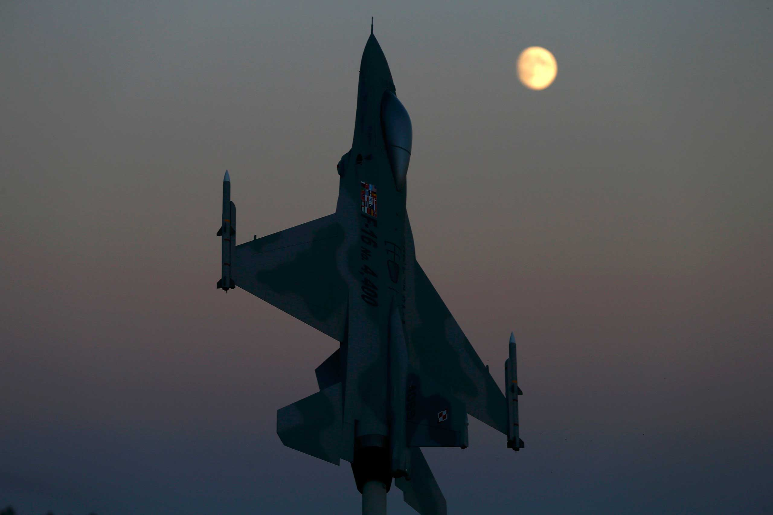 Oct. 6, 2014. A model of an F-16 aircraft, marking the 4,400th F-16 produced and delivered for Poland, is seen at dusk at Lask air base.
