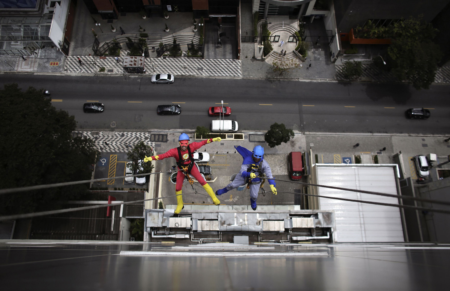 Men dressed as comic book heroes Batman and the Flash gesture as they prepare to clean the glass facade of Hospital Infantil Sabara before meeting with patients of the children's hospital in Sao Paulo on Oct. 7, 2014.
