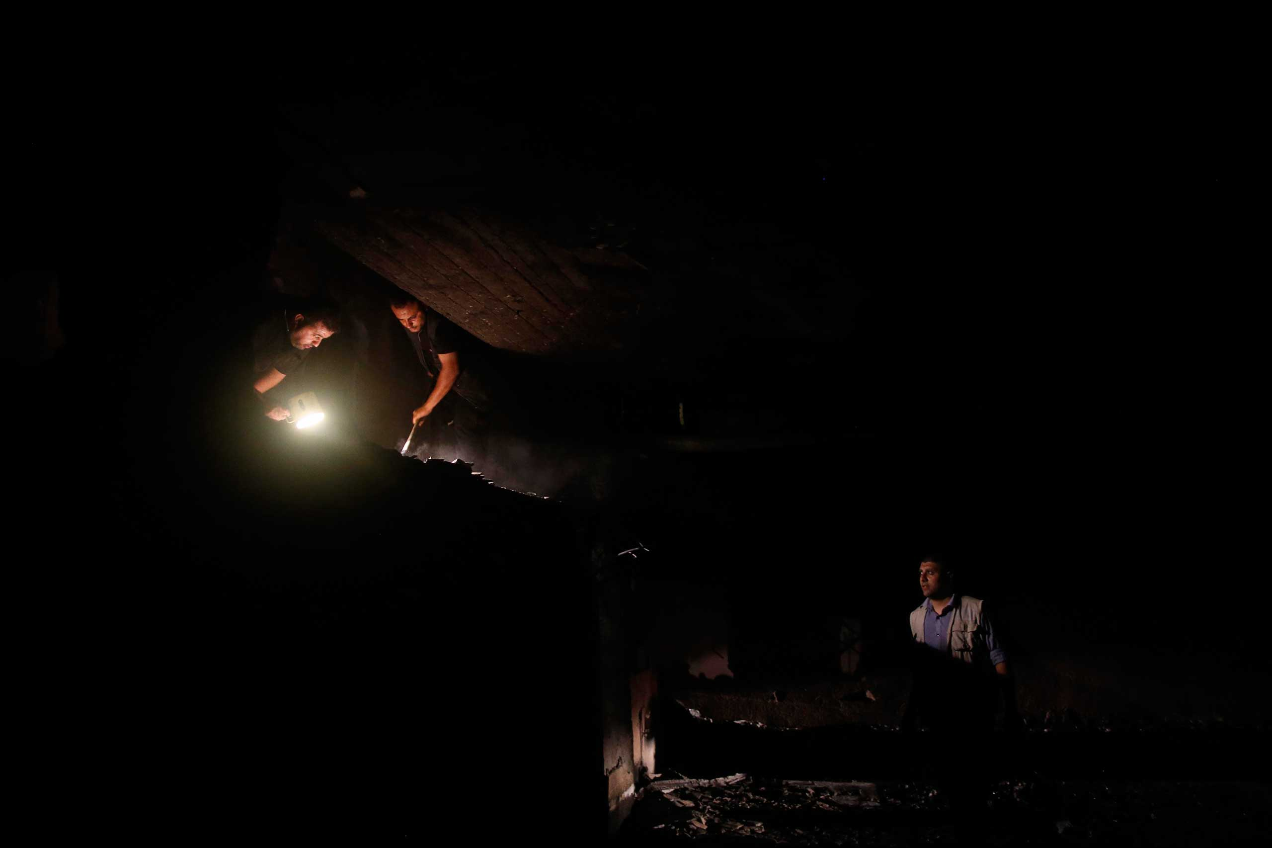 Oct. 7, 2014. Palestinian policemen inspect the damage at the French Culture Center after a fire burned part of the compound following two explosions which were heard at the site in Gaza city. The Gaza interior ministry said it was checking the causes of the incident.