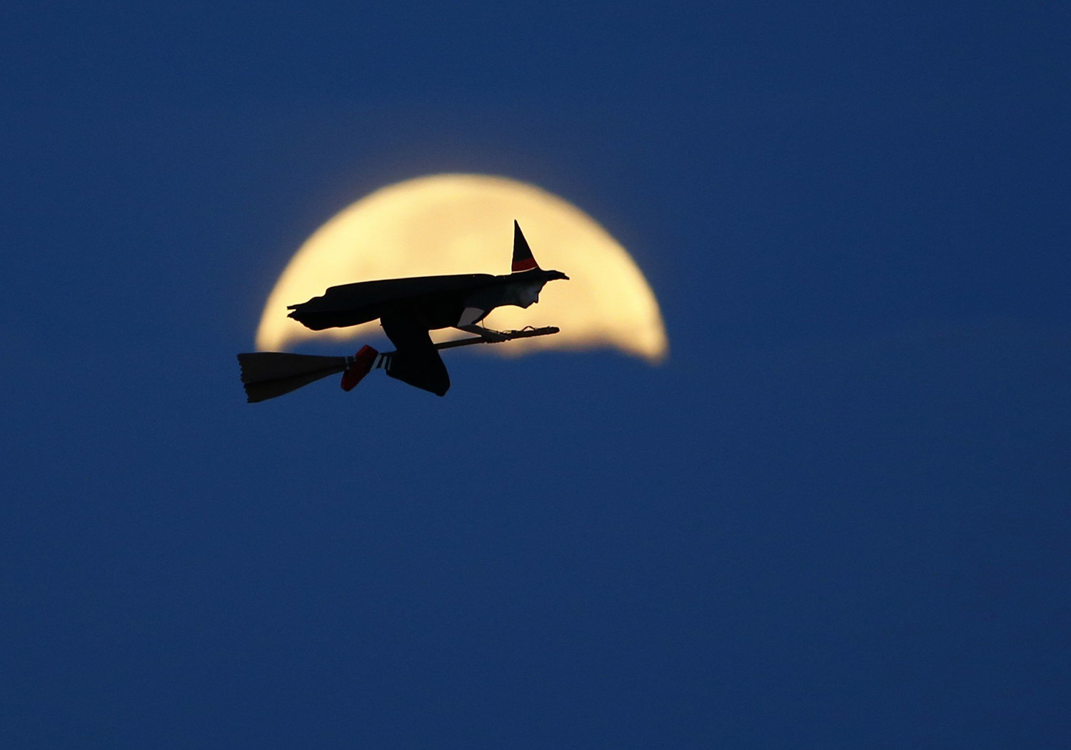 A radio-controlled flying witch makes a test flight  past a moon setting into clouds along the pacific ocean in Carlsbad, Calif. on Oct. 8, 2014.