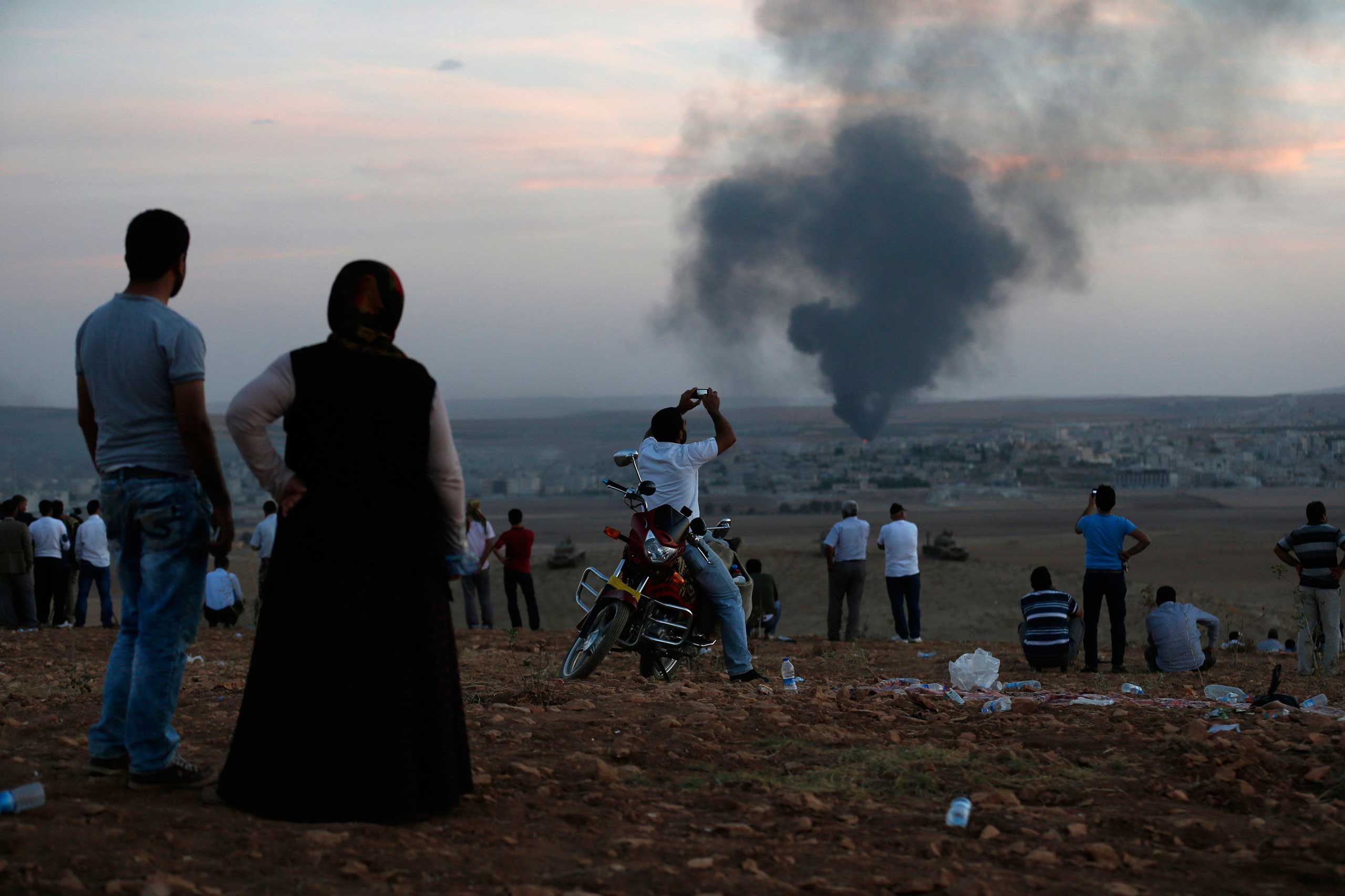 Oct. 9, 2014. Smoke rises in the Syrian town of Kobani as Turkish Kurds watch near the Mursitpinar border crossing on the Turkish-Syrian border in the southeastern town of Suruc.