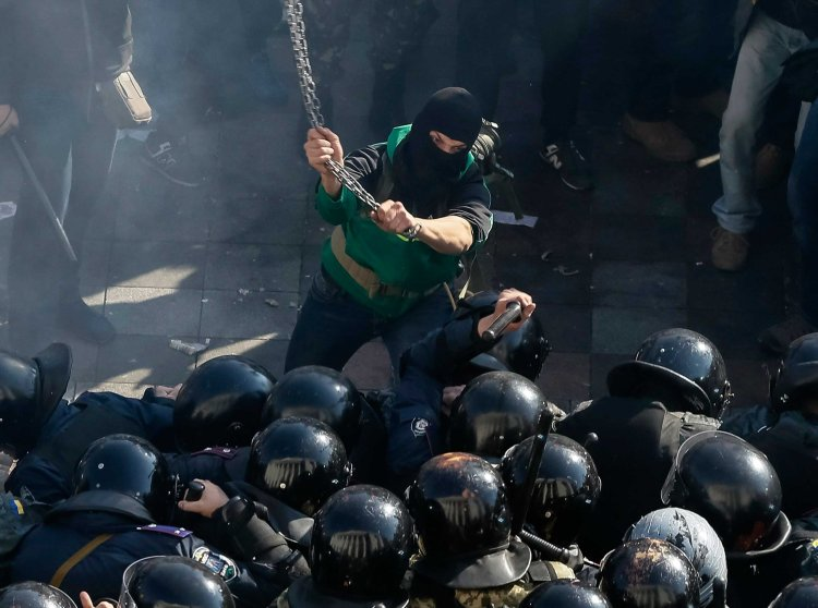 A radical protester clashes with law enforcement members on the Day of Ukrainian Cossacks during a rally near the parliament building in Kiev