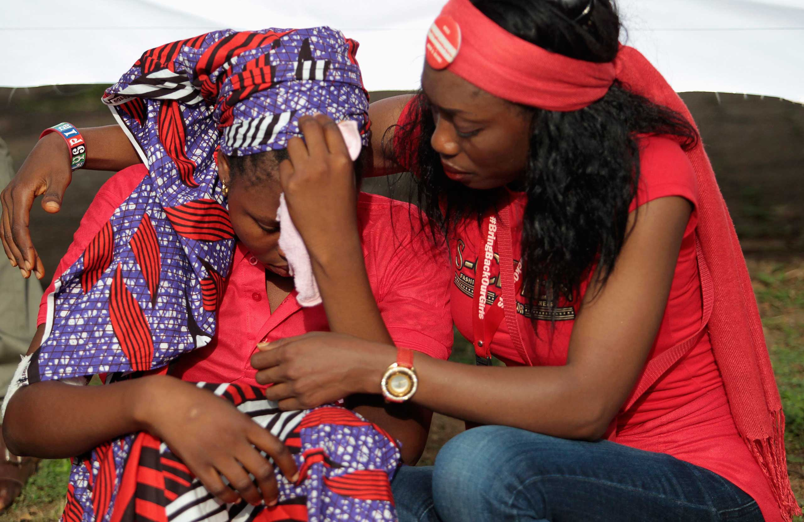 Isaac Rebecca, one of the girls that escaped from the Boko Haram camp is comforted during a protest march to the Presidential Villa, in Abuja Oct. 14, 2014.