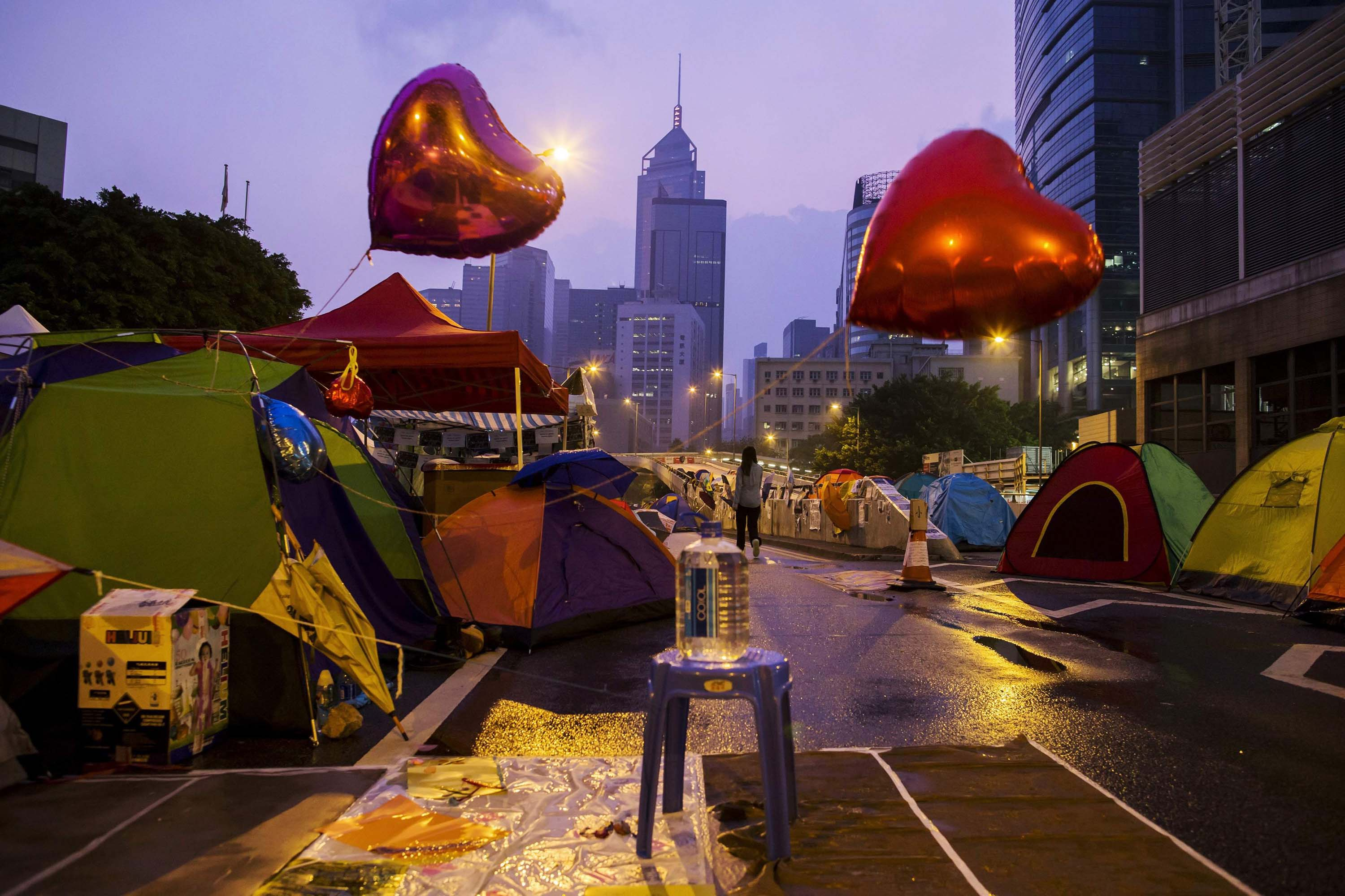 An Occupy Central protester walks past tents before sunrise on a main road leading to the financial Central district in Hong Kong on Oct. 16, 2014.