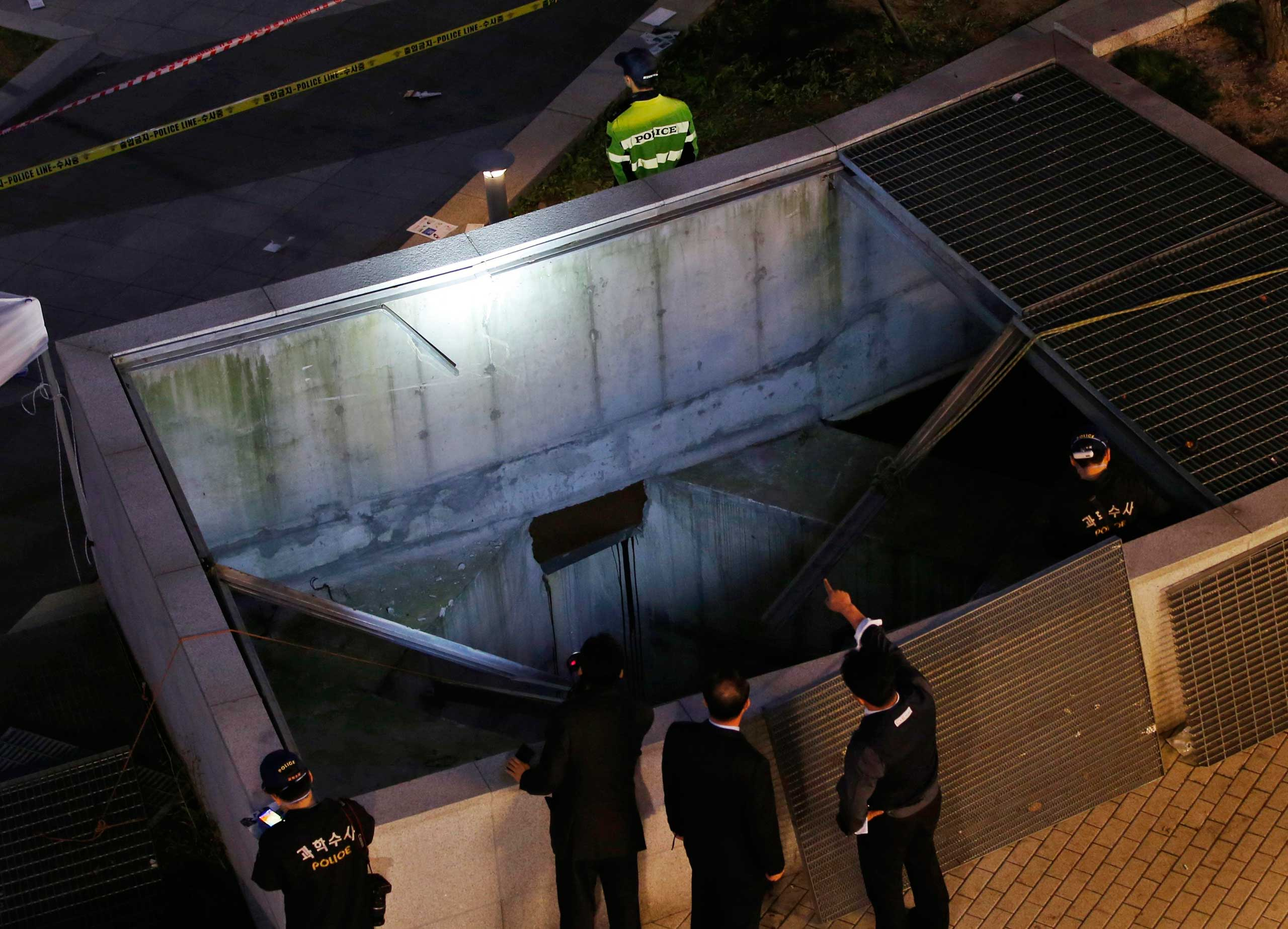Oct. 17, 2014. Police officials examine the scene of an accident at a shopping district in Seongnam. Fourteen people were killed at a open-air pop concert in South Korea on Friday when the cover of a ventilation shaft they were standing on gave way, officials and media said.