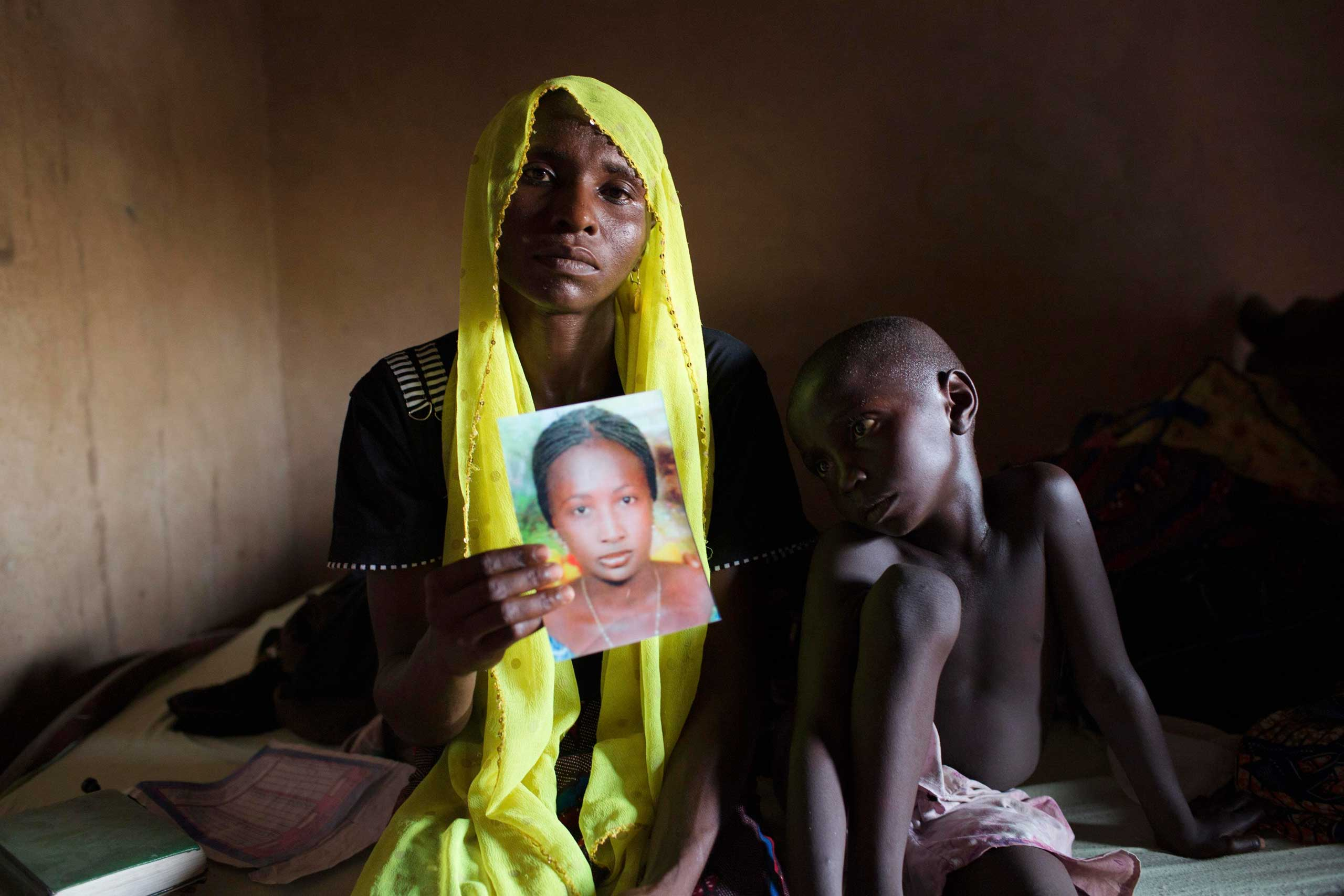Rachel Daniel, 35, holds up a picture of her abducted daughter Rose Daniel, 17, as her son Bukar, 7, sits beside her at her home in Maiduguri, May 21, 2014. Boko Haram kidnapped an additional 30 boys and girls from a village in northeast Nigeria during the weekend.