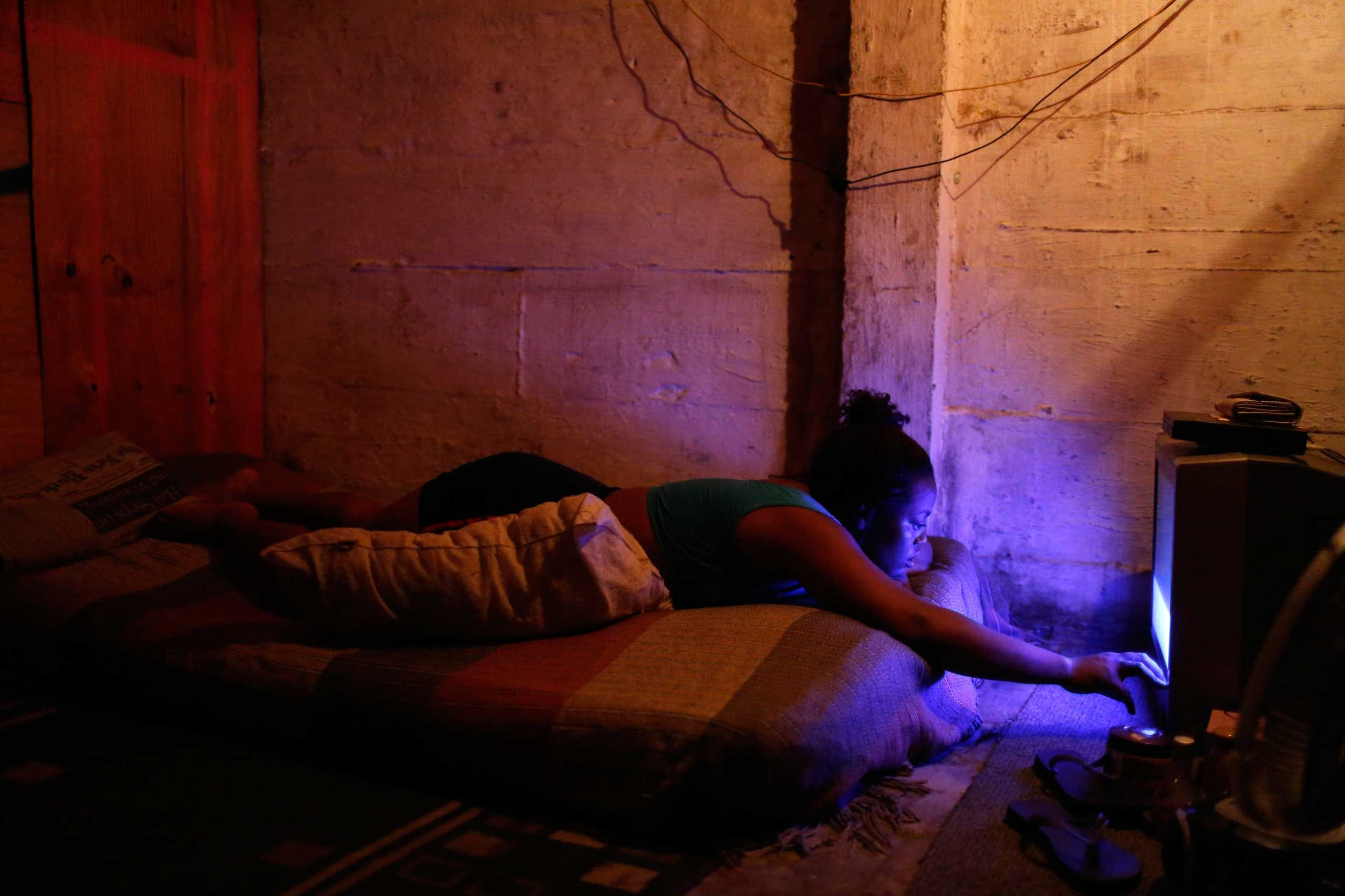 Oct. 17, 2014. A woman watches television inside her makeshift home at the Nova Tuffy slum in an abandoned factory in Rio de Janeiro. 1,800 families have been living inside the factory since March, with poor sanitation services and the fear of eviction.
