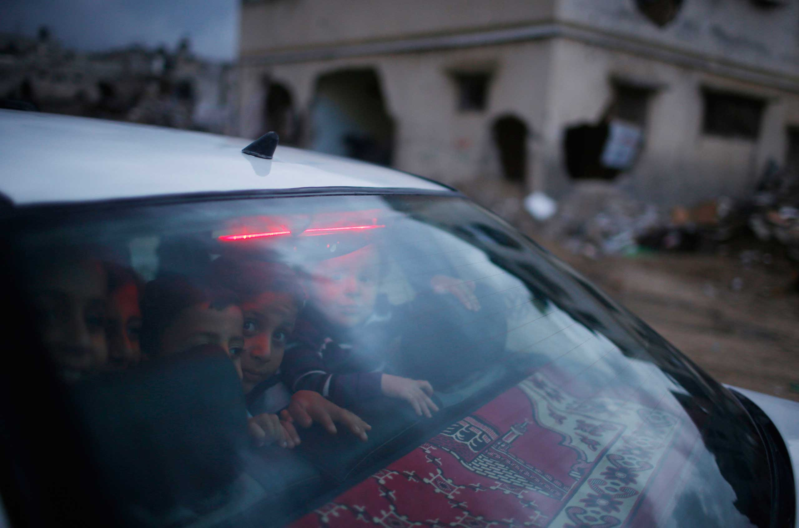 Oct. 19, 2014. Palestinian children look out of the rear windscreen of a car as they pass damaged houses in the east of Gaza City. An open-ended ceasefire between Israel and Hamas-led Gaza militants, mediated by Egypt, took effect on August 26 after a seven-week conflict.