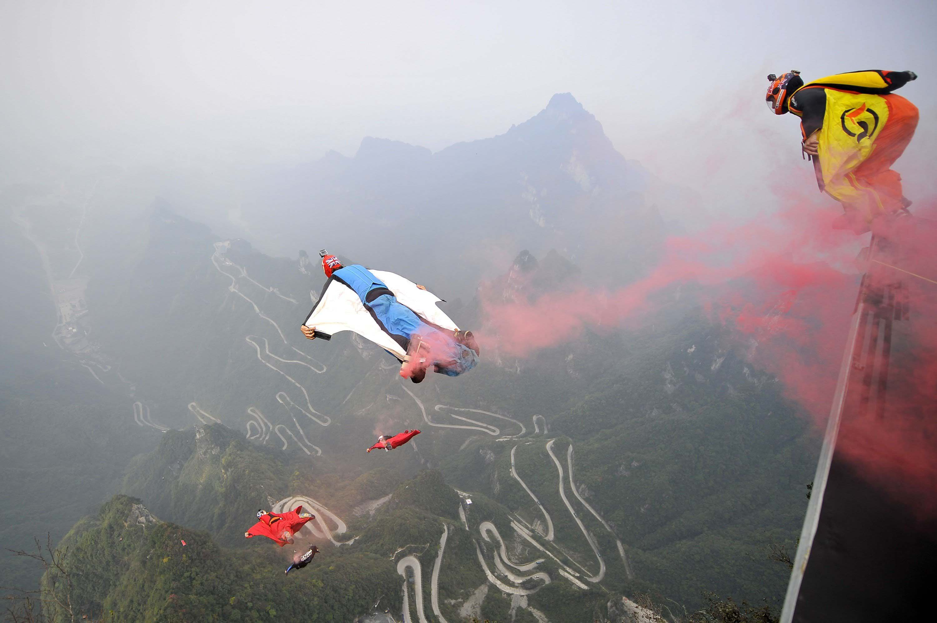Wingsuit flyer contestants jump off a mountain at Tianmen Mountain National Park in Zhangjiajie, Hunan province, China on Oct. 19, 2014.