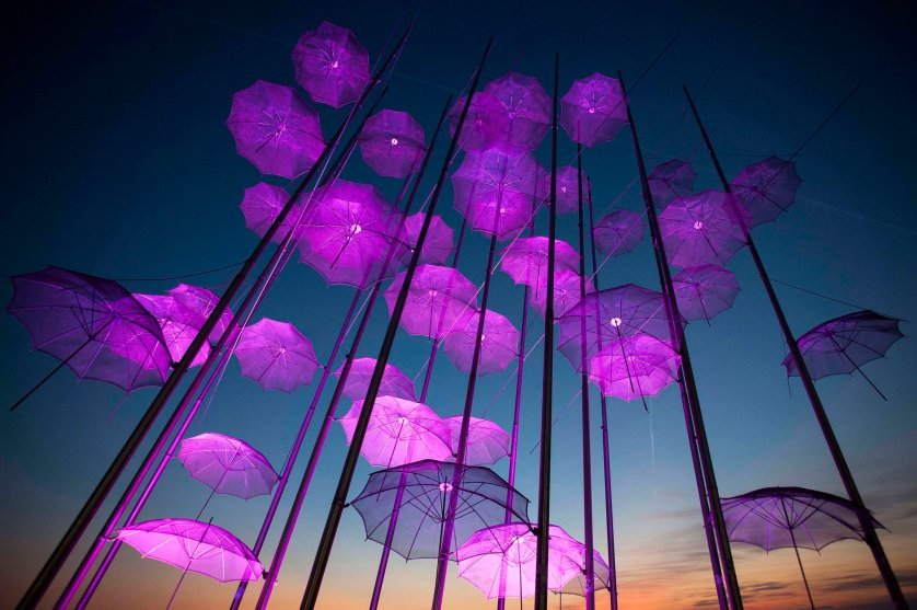 """""""Umbrellas"""", the sculpture by Giorgos Zogolopoulos is illuminated in pink light to mark Breast Cancer Awareness Month in Thessaloniki in northern Greece on Oct. 21, 2014."""