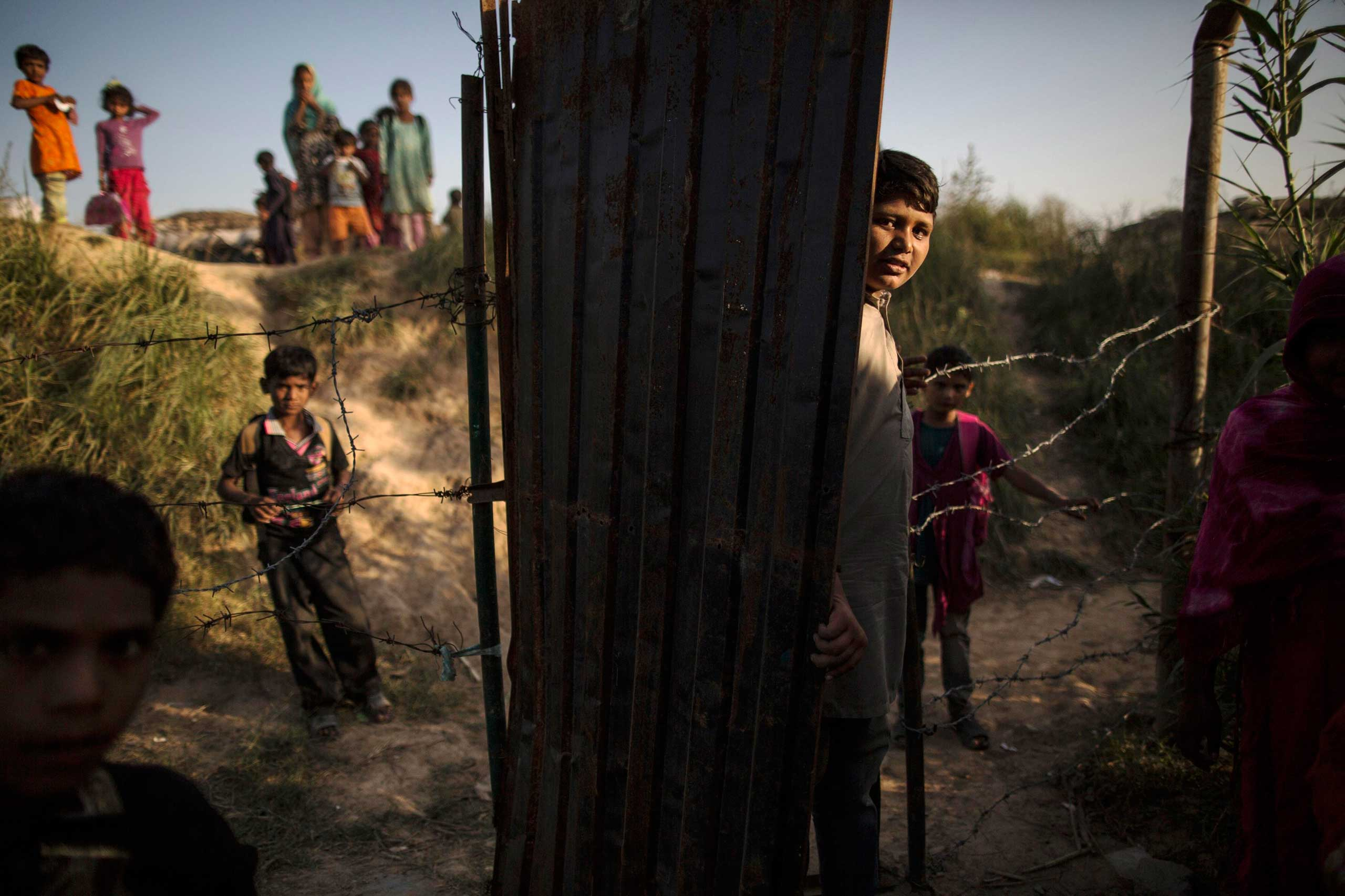 Oct. 22, 2014. Children, whose family moved to Islamabad from Sargodha in Punjab Province to look for work, stand outside their school at a slum in Islamabad.