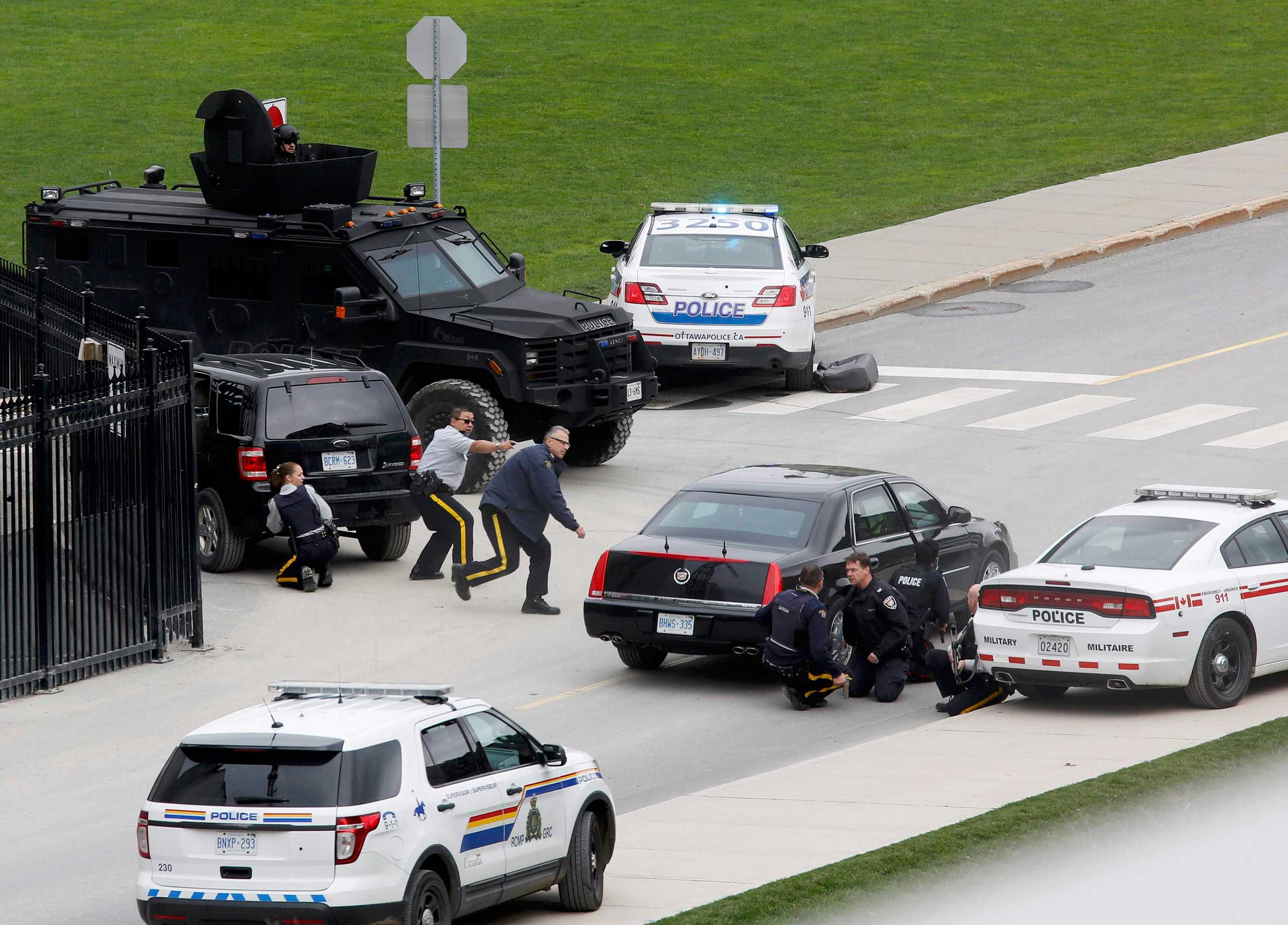 Oct. 22, 2014. Police officers take cover near Parliament Hill following a shooting incident in Ottawa. A Canadian soldier was shot at the Canadian War Memorial and a shooter was seen running towards the nearby parliament buildings, where more shots were fired, according to media and eyewitness reports.