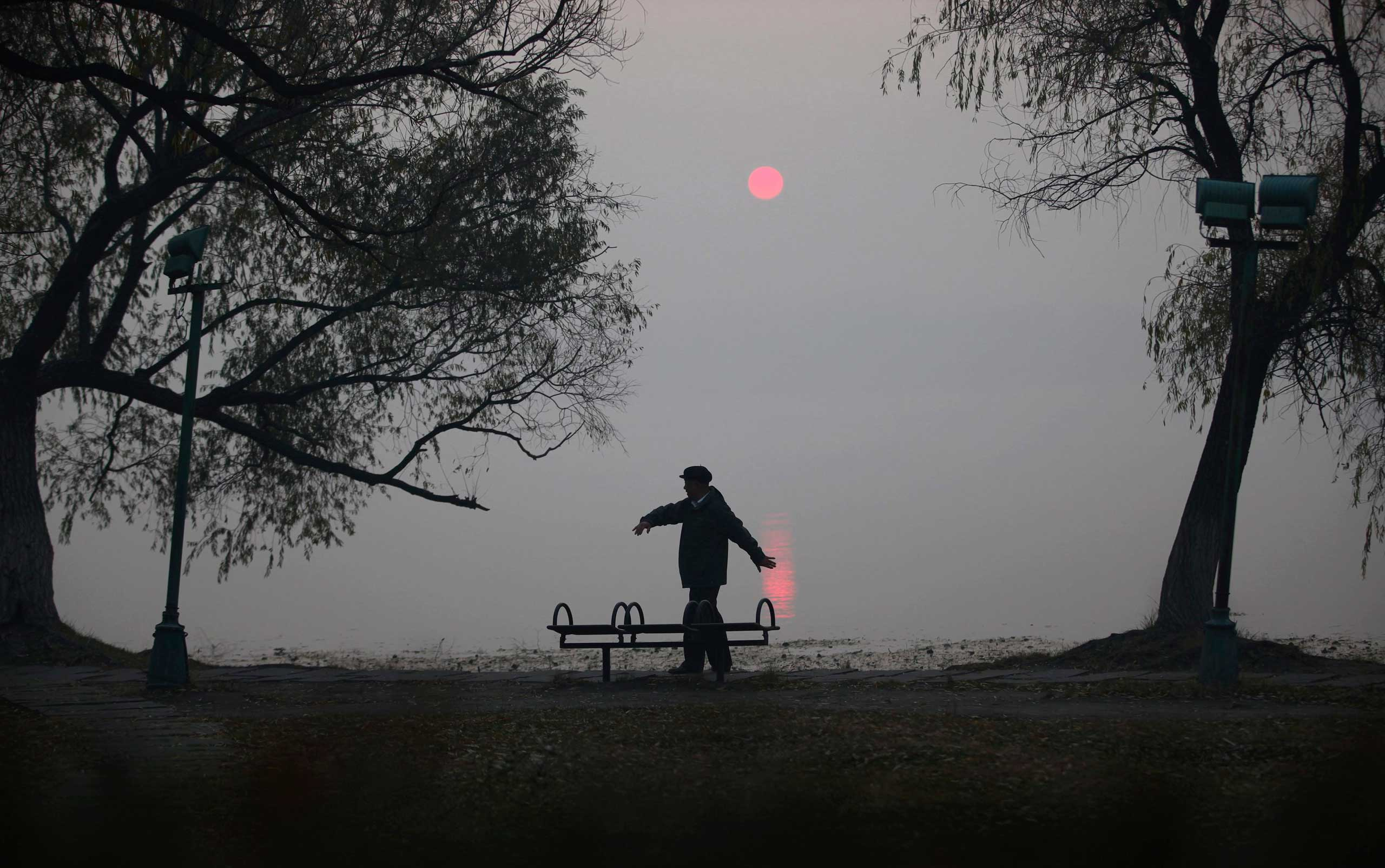 Oct. 22, 2014. A man does his morning exercise on a polluted day by the side of a lake at Nanhu Park in Changchun, Jilin province.