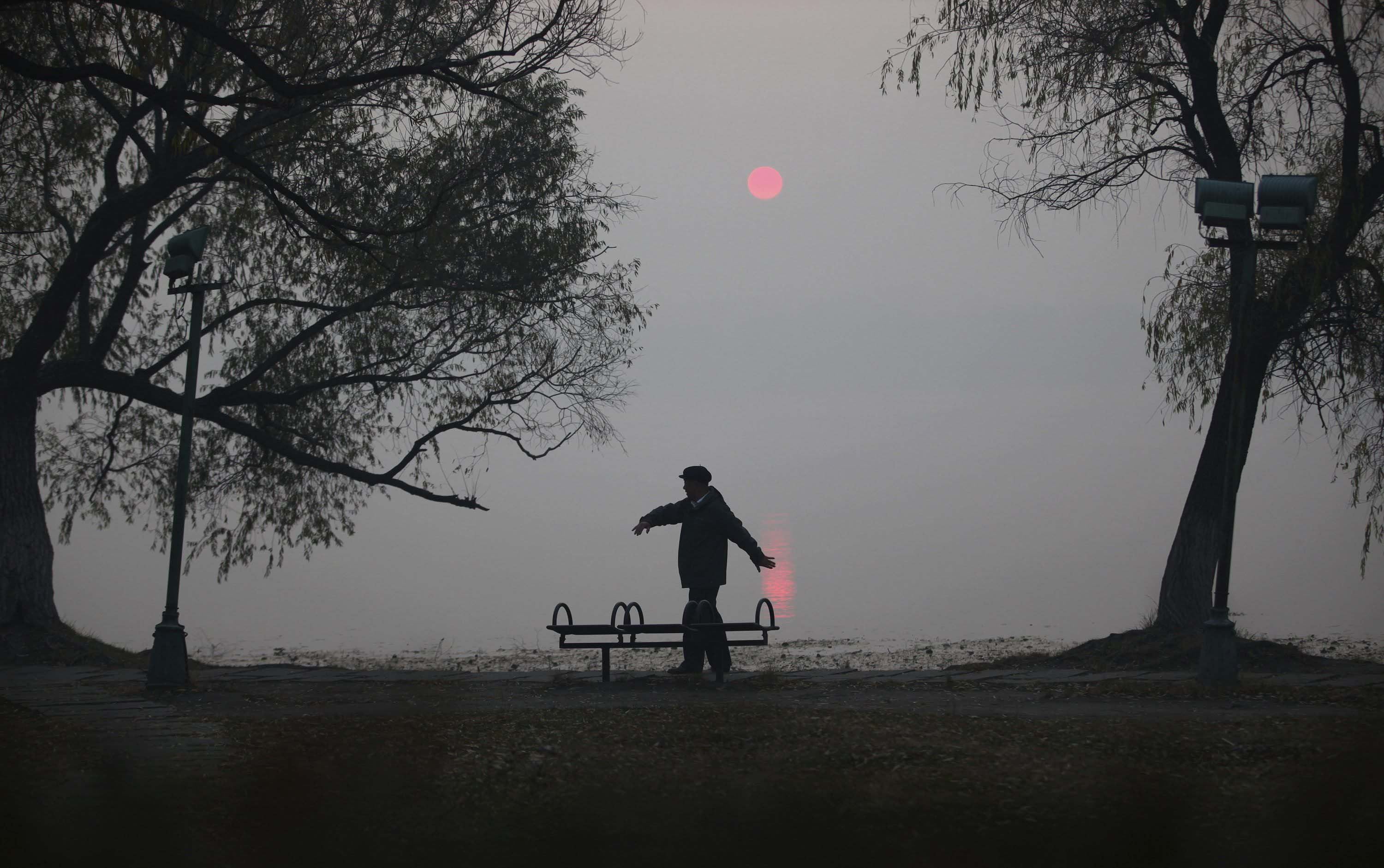 A man does his morning exercise on a polluted day by the side of a lake at Nanhu Park in Changchun, Jilin province, China on Oct. 22, 2014.