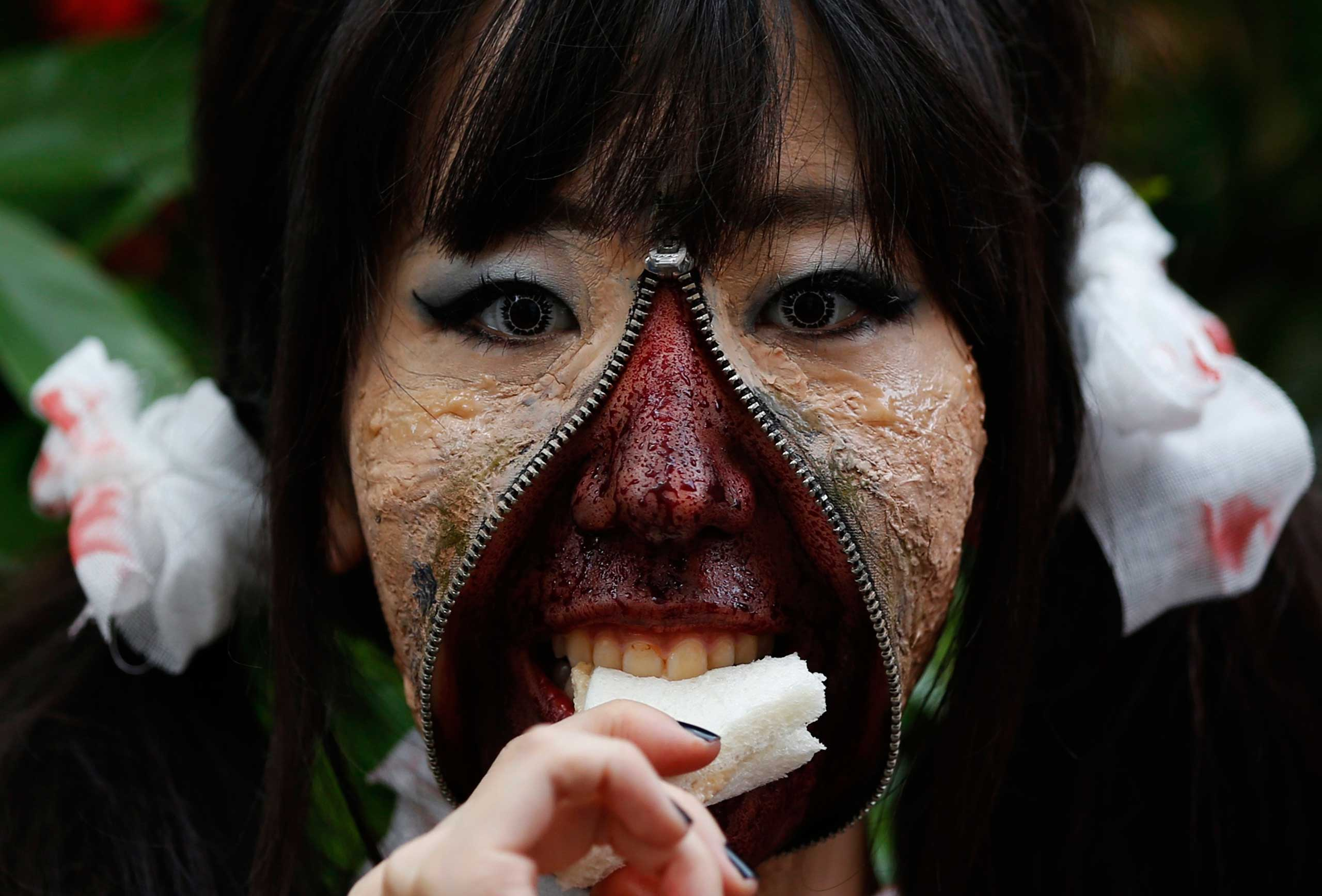 Oct. 26, 2014. A participant in costume eats a sandwich after a Halloween parade in Kawasaki, south of Tokyo. More than 100,000 spectators turned up to watch the parade, where 2,500 participants dressed up in costumes, according to the organizer.