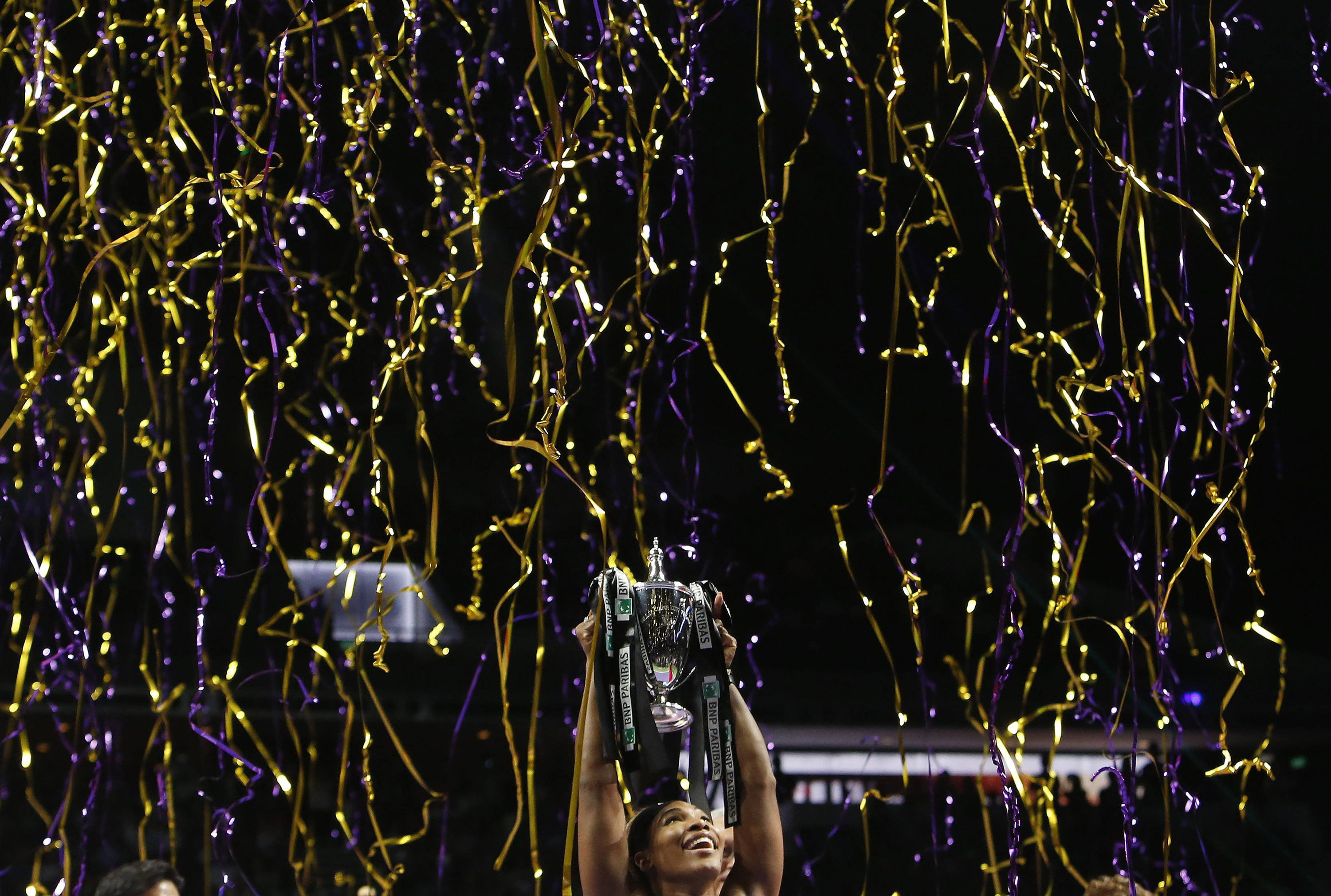 Serena Williams of the U.S. poses with the trophy after defeating Simona Halep of Romania in the women's singles final tennis match of the WTA Finals at the Singapore Indoor Stadium on October 26, 2014.