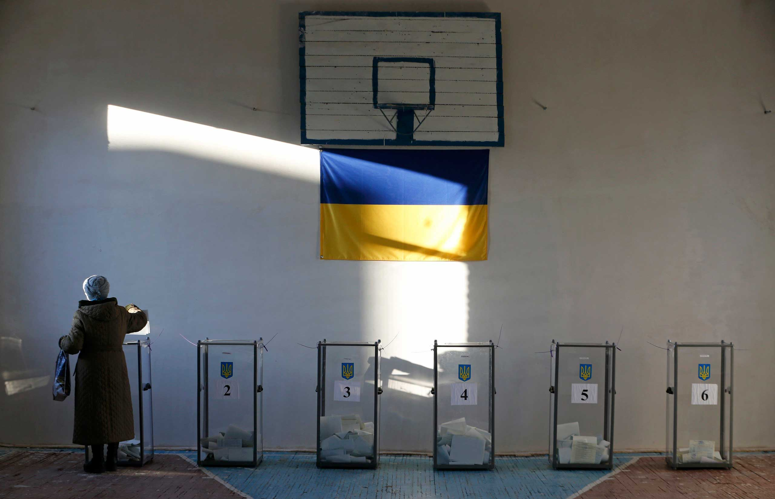 Oct. 26, 2014. A woman casts a ballot during a parliamentary election at a school gym in the village of Semyonovka near Slaviansk, eastern Ukraine. Ukrainians voted on Sunday in an election that is likely to install a pro-Western parliament and strengthen President Petro Poroshenko's mandate to end separatist conflict in the east, but may fuel tension with Russia.