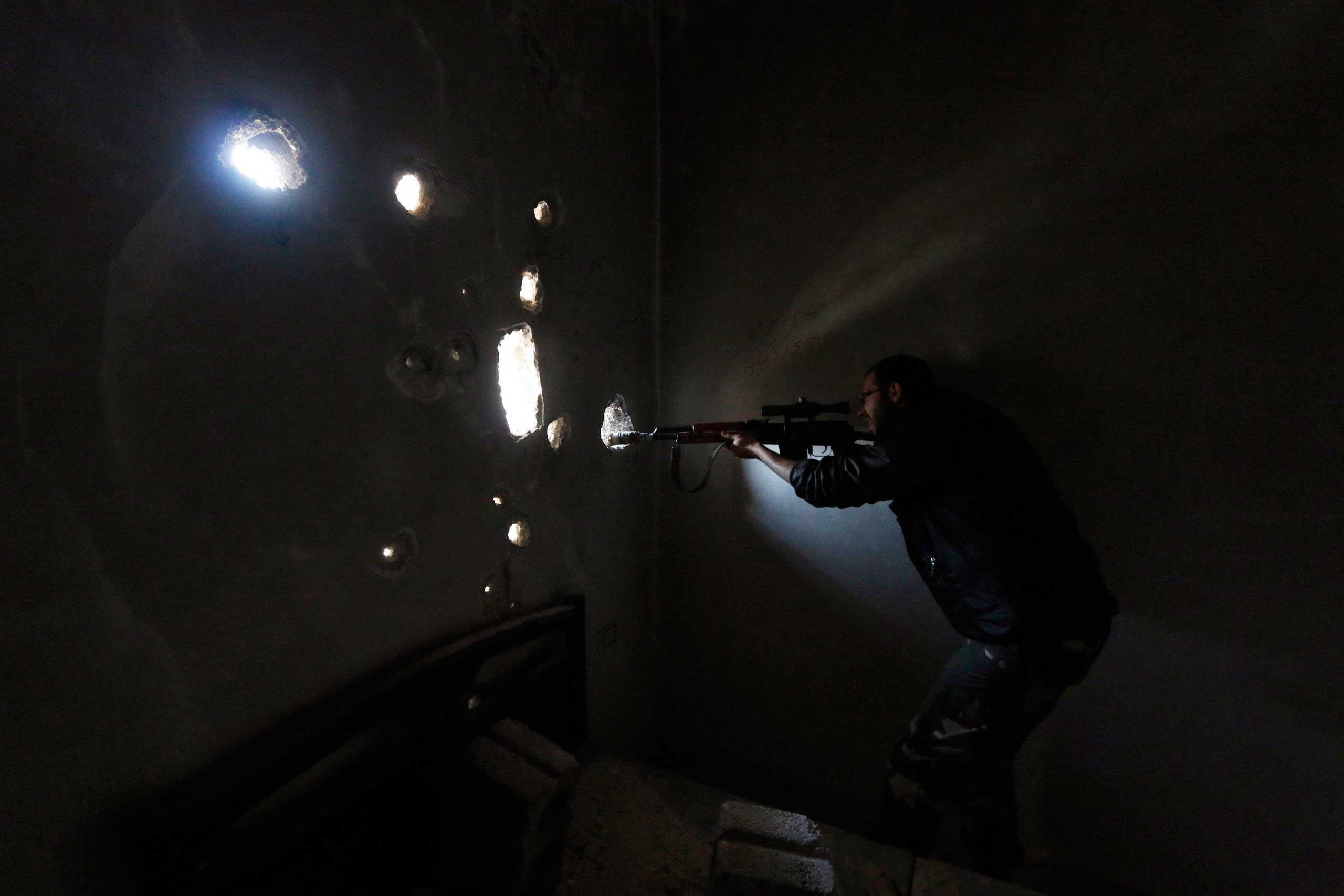 Oct. 26, 2014.  A Free Syrian Army fighter carrying a weapon looks through a hole in the wall inside a damaged building on the frontline of Aleppo's Al-Ezaa neighborhood.