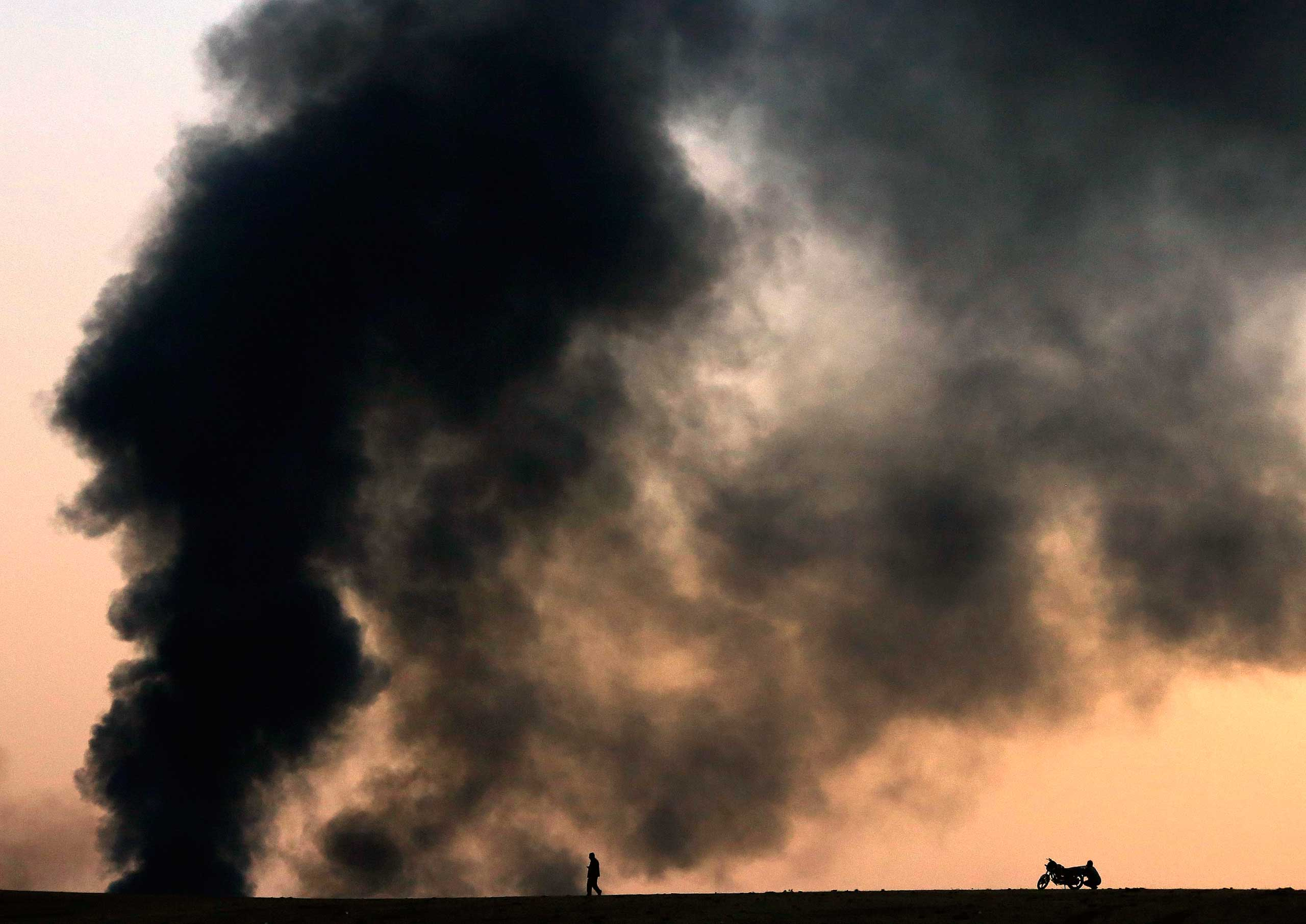 Oct. 26, 2014. Kurdish refugees watch from a hilltop as thick smoke rises from the Syrian town of Kobani during heavy fighting between Islamic State (ISIS) and Kurdish Peshmerga forces, seen from near the Mursitpinar border crossing on the Turkish-Syrian border in the southeastern town of Suruc in Sanliurfa Province.