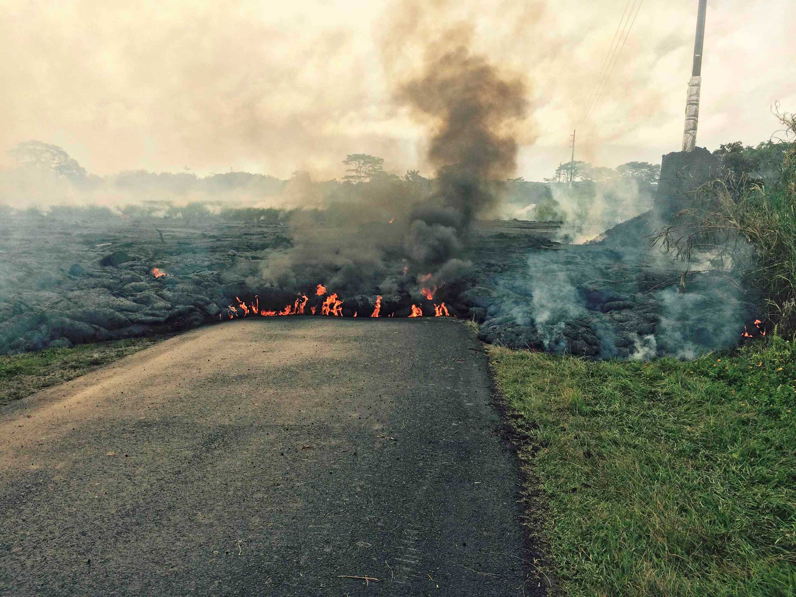 The lava flow from the Kilauea Volcano is seen crossing Apa'a Street/Cemetery Road in this U.S. Geological Survey (USGS) image taken near the village of Pahoa, Hawaii Oct. 25, 2014.
