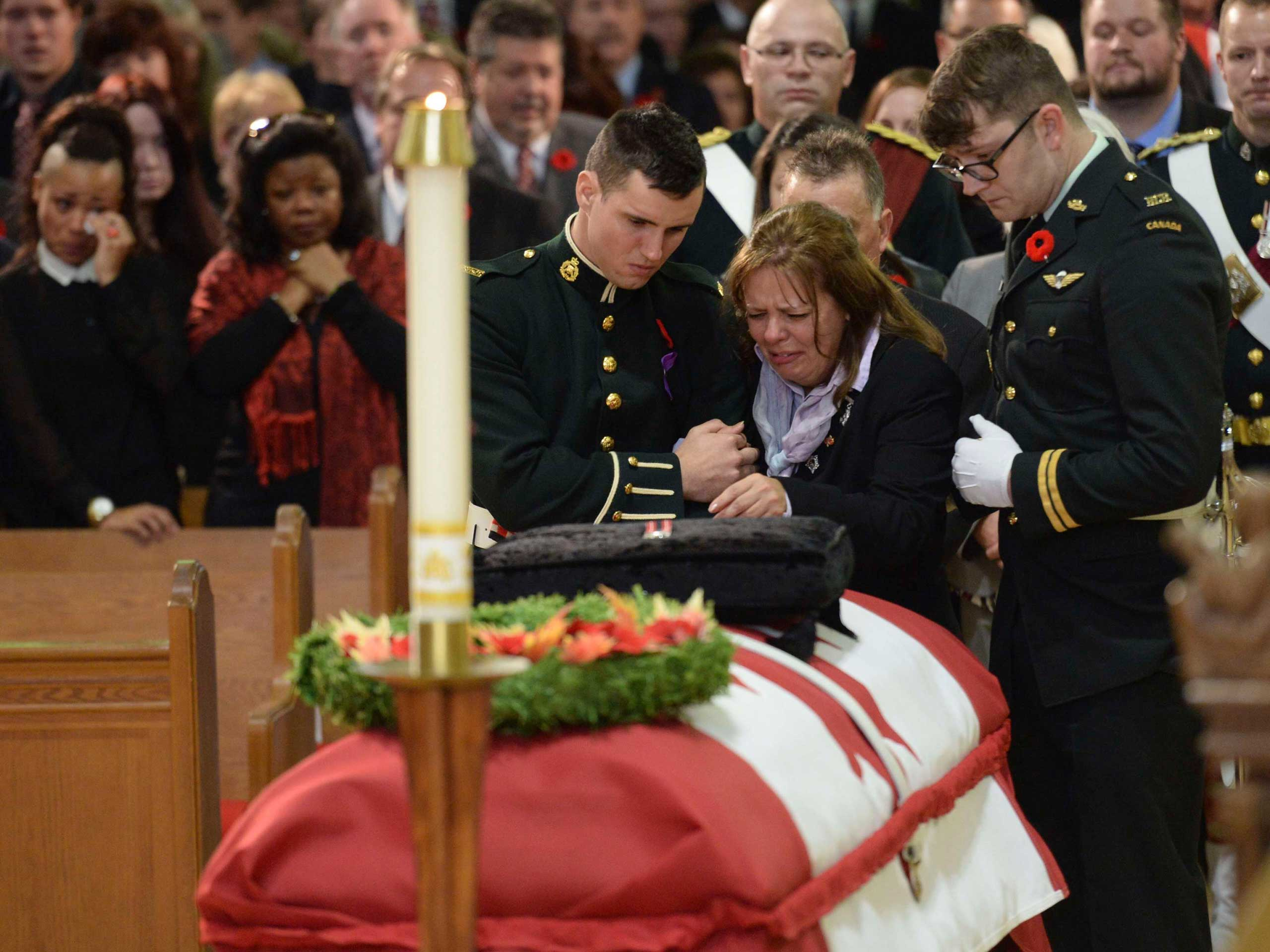 Oct. 28, 2014. Kathy Cirillo is comforted in front of the coffin of her son Cpl. Nathan Cirillo at his regimental funeral service in Hamilton, Ontario Province, Canada. Cirillo was standing guard at the National War Memorial in Ottawa last Wednesday when he was killed by a gunman who went on to open fire on Parliament Hill.