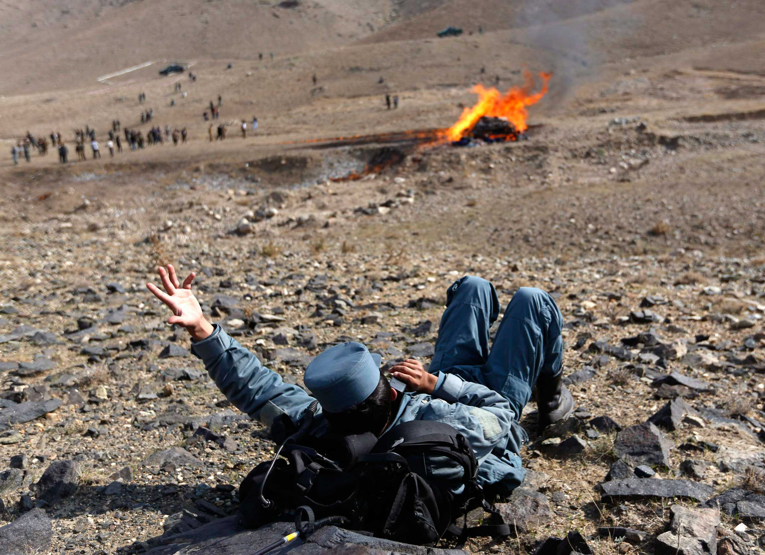 Oct. 29, 2014. An Afghan policeman talks on his phone during the burning of illegal narcotics on the outskirts of Kabul. Over 20 tons of narcotics, seized by Afghan security forces, were destroyed by the police on Wednesday, the U.N. Office on Drugs and Crime (UNODC) said.