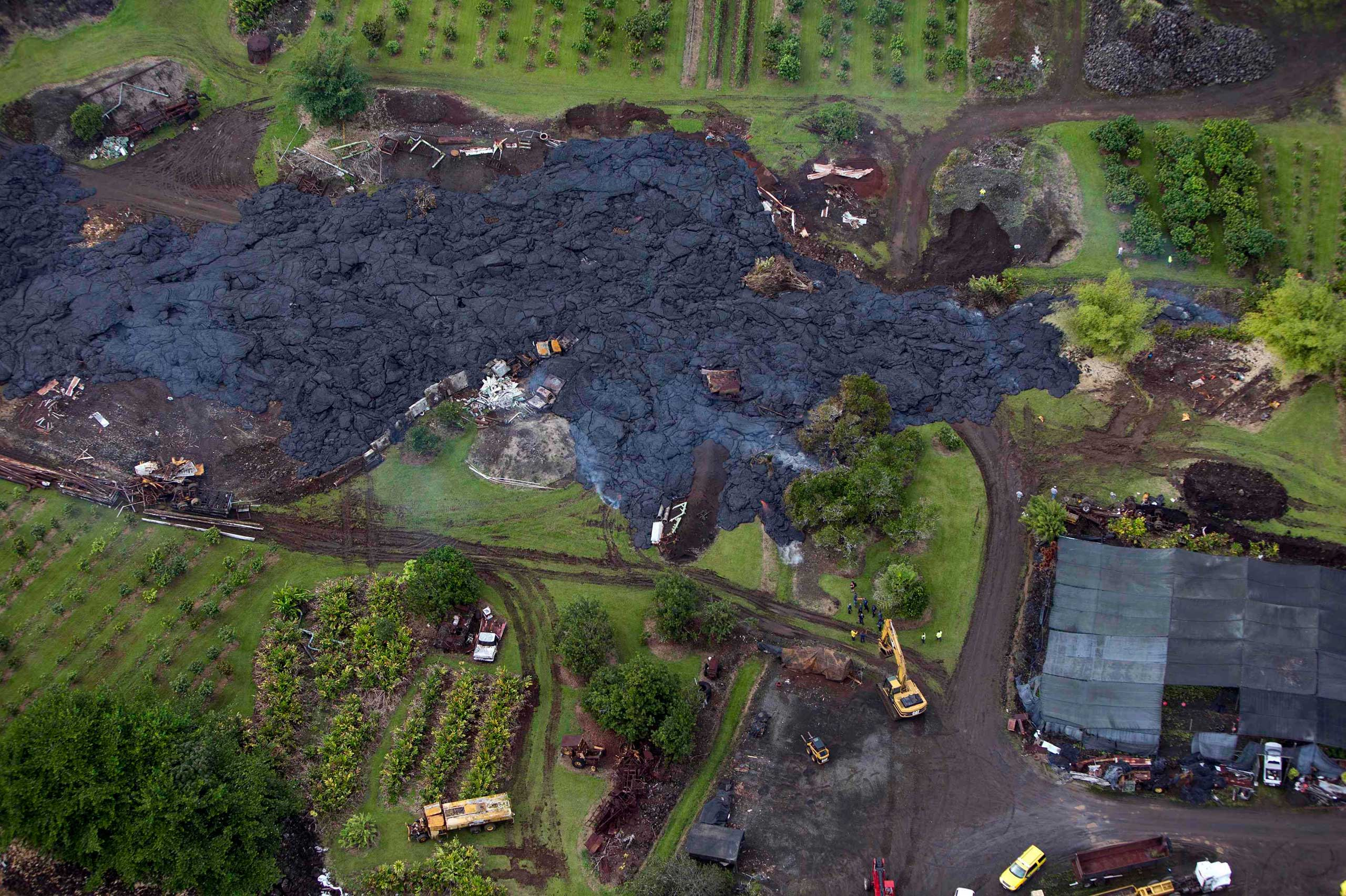 Oct. 29, 2014. Construction crews try divert lava from Mt. Kilauea from a home in the village of Pahoa, Hawaii. A slow-moving river of molten lava from an erupting volcano crept over residential and farm property on Hawaii's Big Island on Wednesday after incinerating an outbuilding as it threatened dozens of homes at the edge of a former plantation town.