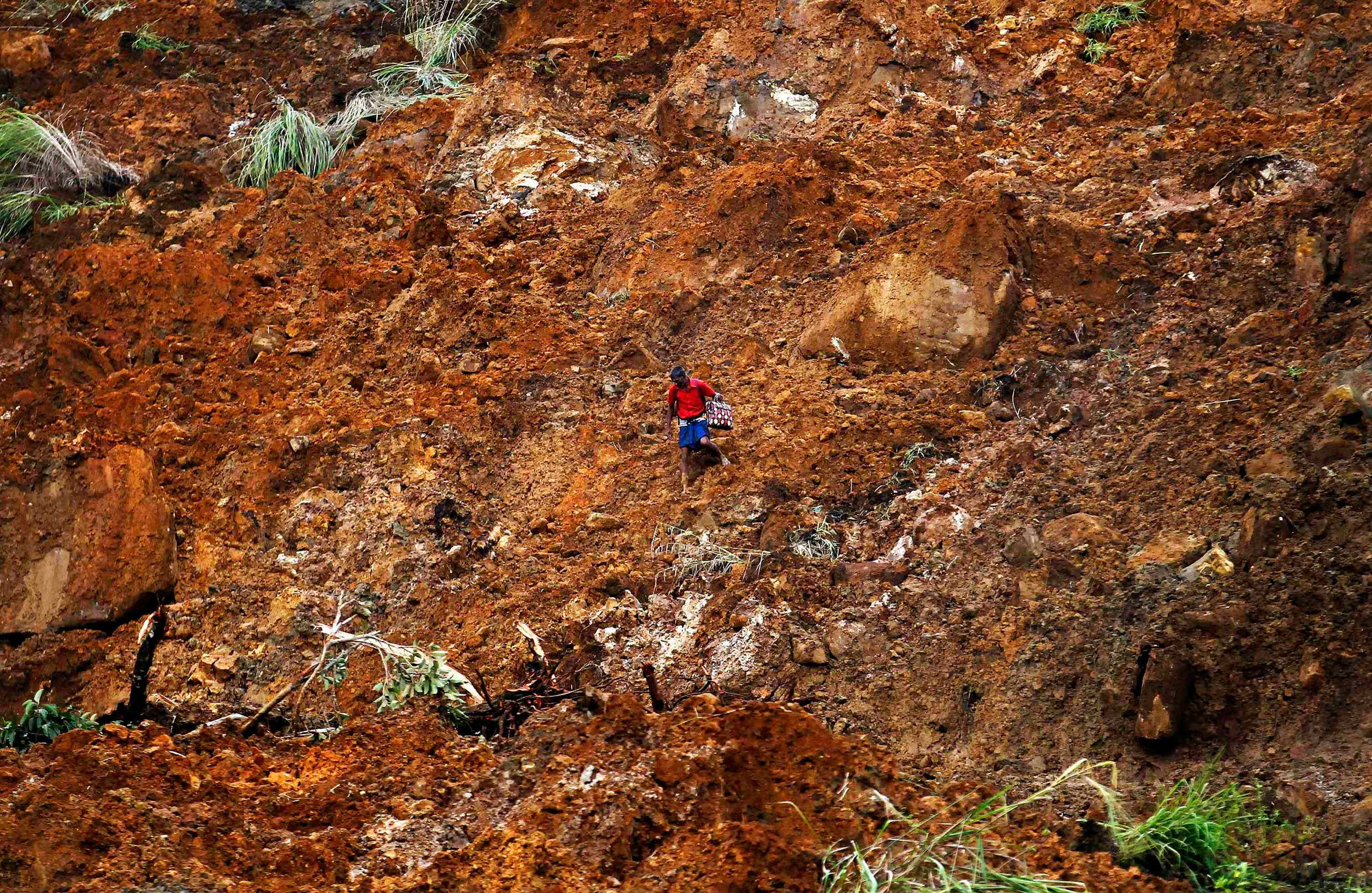Oct. 30, 2014. A man carrying a suitcase crosses a muddy slope at the site of a landslide at the Koslanda tea plantation near Haldummulla. Hopes of finding survivors under the mud and rubble of the landslide in south-central Sri Lanka had run out by first light on Thursday, though a government minister cut the estimated death toll to more than 100 from 300 the previous night.