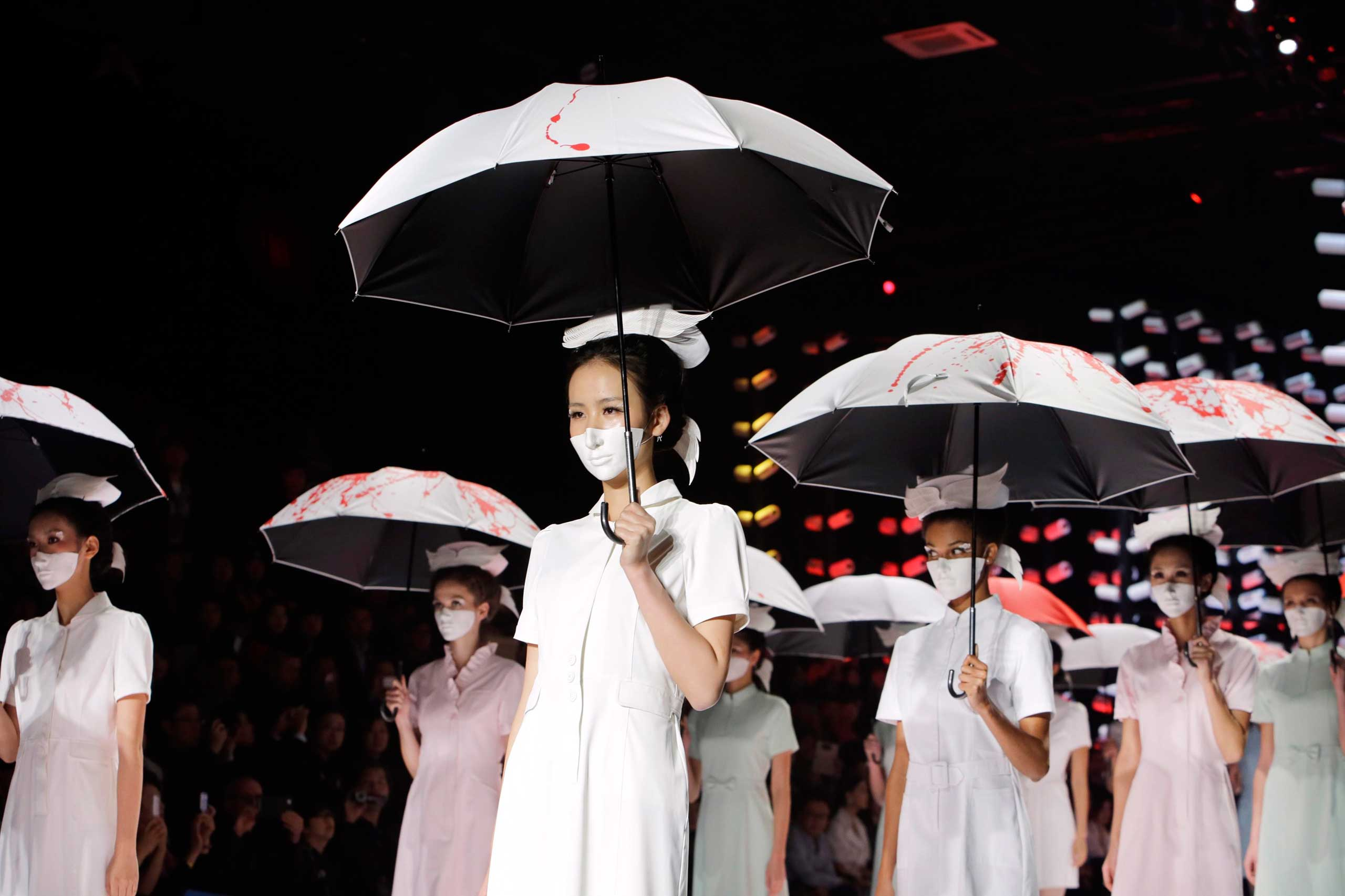Oct. 30, 2014. Models wearing masks hold umbrellas as they perform during the Toray Liu Wei Collection segment at China Fashion Week in Beijing.